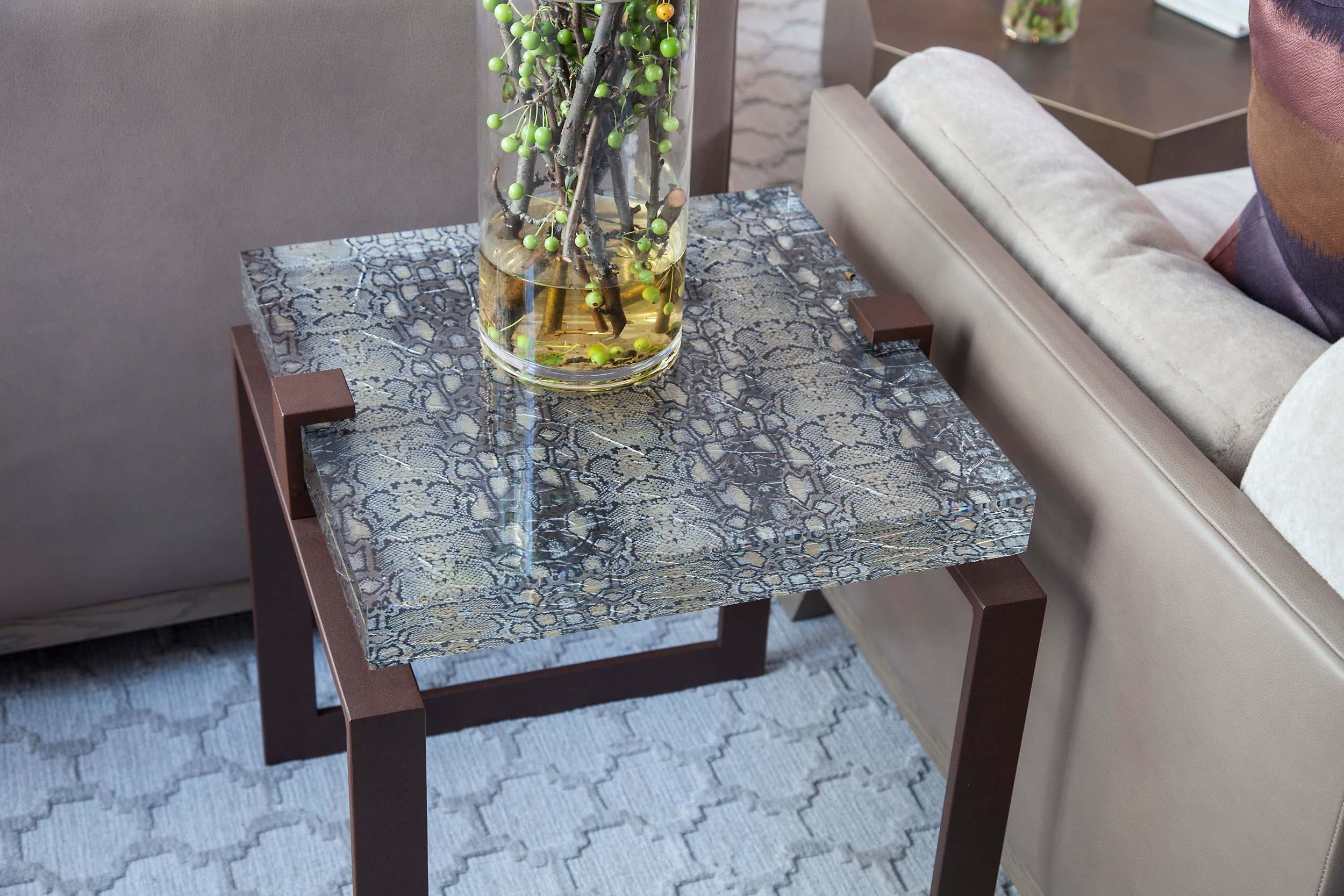 This snake skin and metal vintage glass side table along with fresh crabtree branches add color and texture.