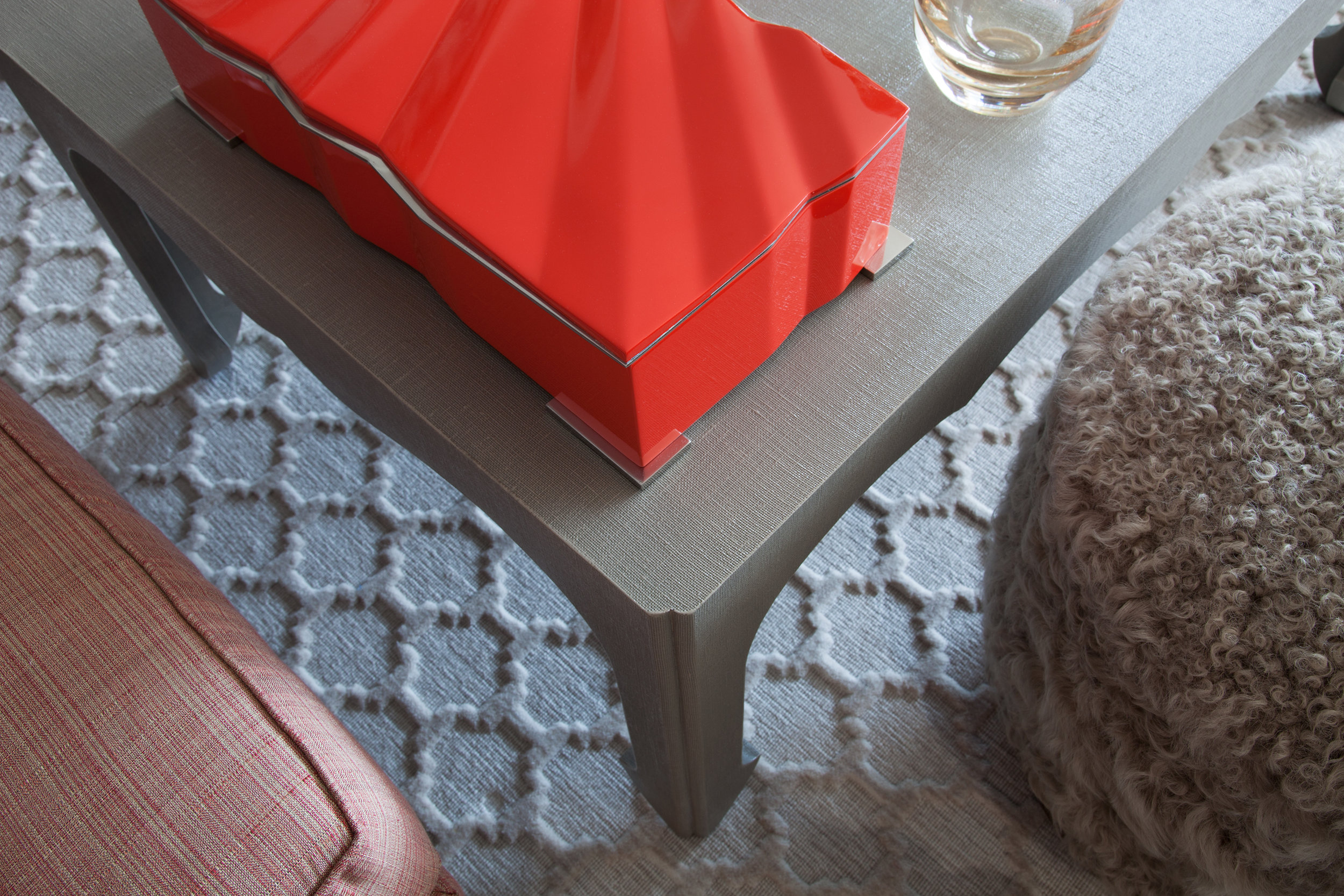 This rug was the starting point for the room. The geometric pattern plays off of the strie fabric on the club chairs and the linen wrapped parsons coffee table. The Mongolian wool stool brings a fun touch of contrasting texture to the room.