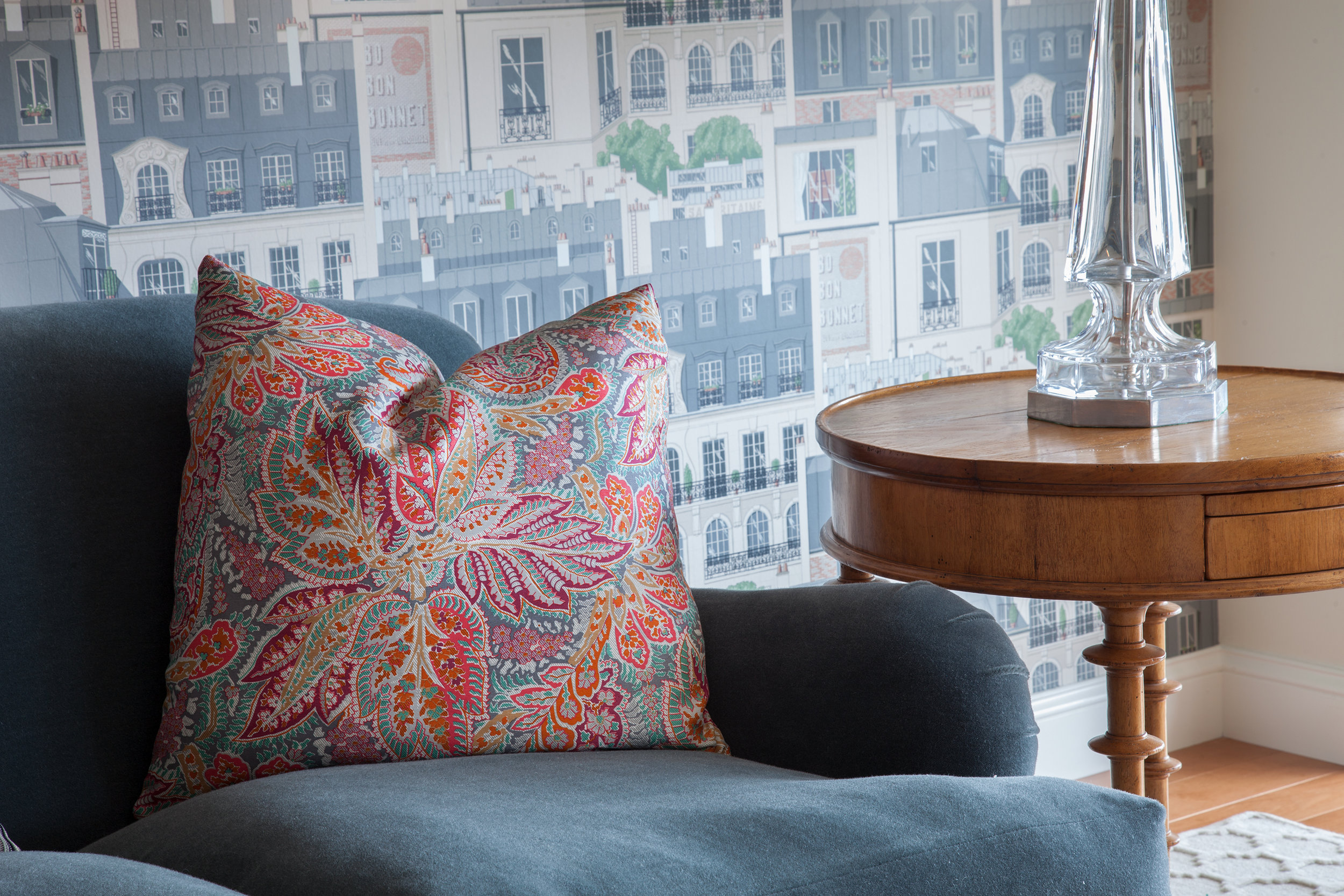 A playful Paris city scene wallpaper contrasts the colorful floral pillows. Crystal table lamps bring a sparkle to the room.