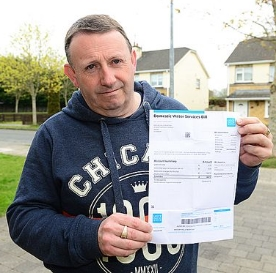 Michael Murtagh holds up a water bill that daughter Michelle received despite living in Canada for two years