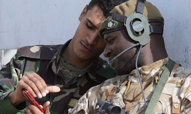 A British soldier looks at an Iraqi colleague's mobile phone during a joint patrol. Photograph: Matt Cardy/Getty Images