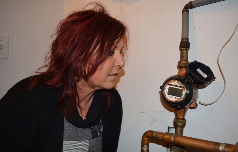 Eva Austin inspects a water meter. The local realtor has heard several complaints about high water bills in recent months and is concerned over water meter issues with the town.