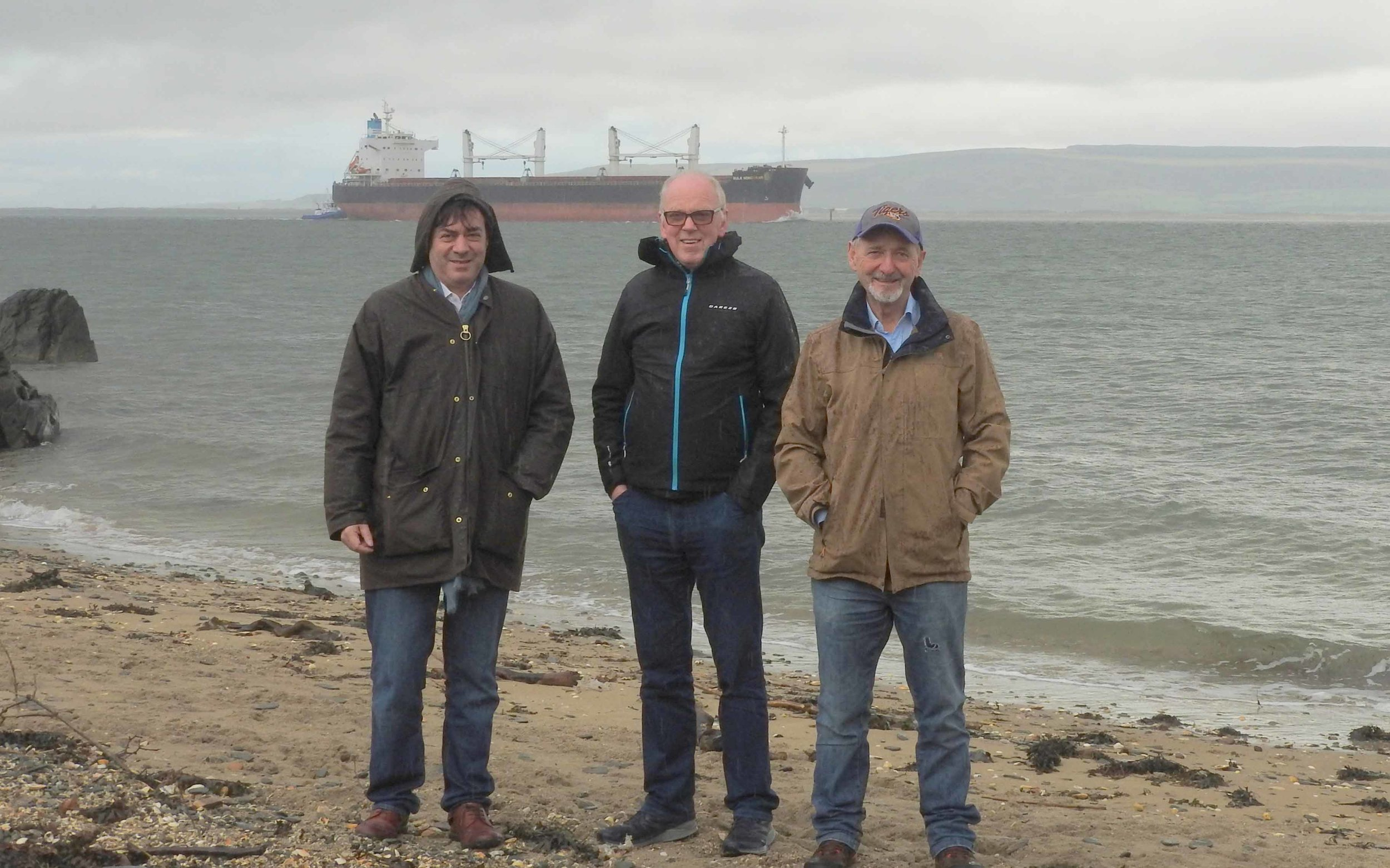 Campaigners John Gore, Dr Don McGinley and Enda Craig at the site where the outfall will carry sewage into Lough Foyle behind them. Image: Paddy Clancy.