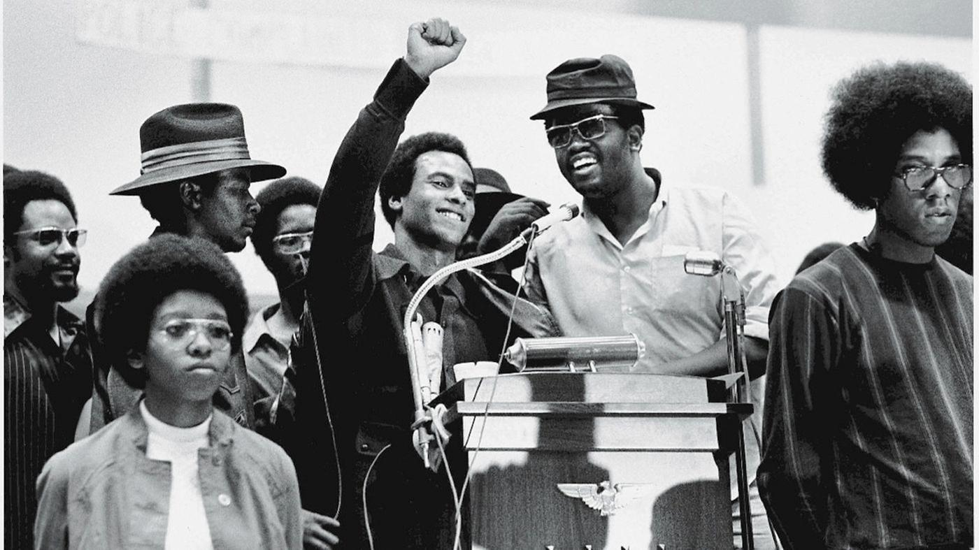 Huey Newton, co-founder of the Black Panther Party, has right arm raised next to speaker at lectern.