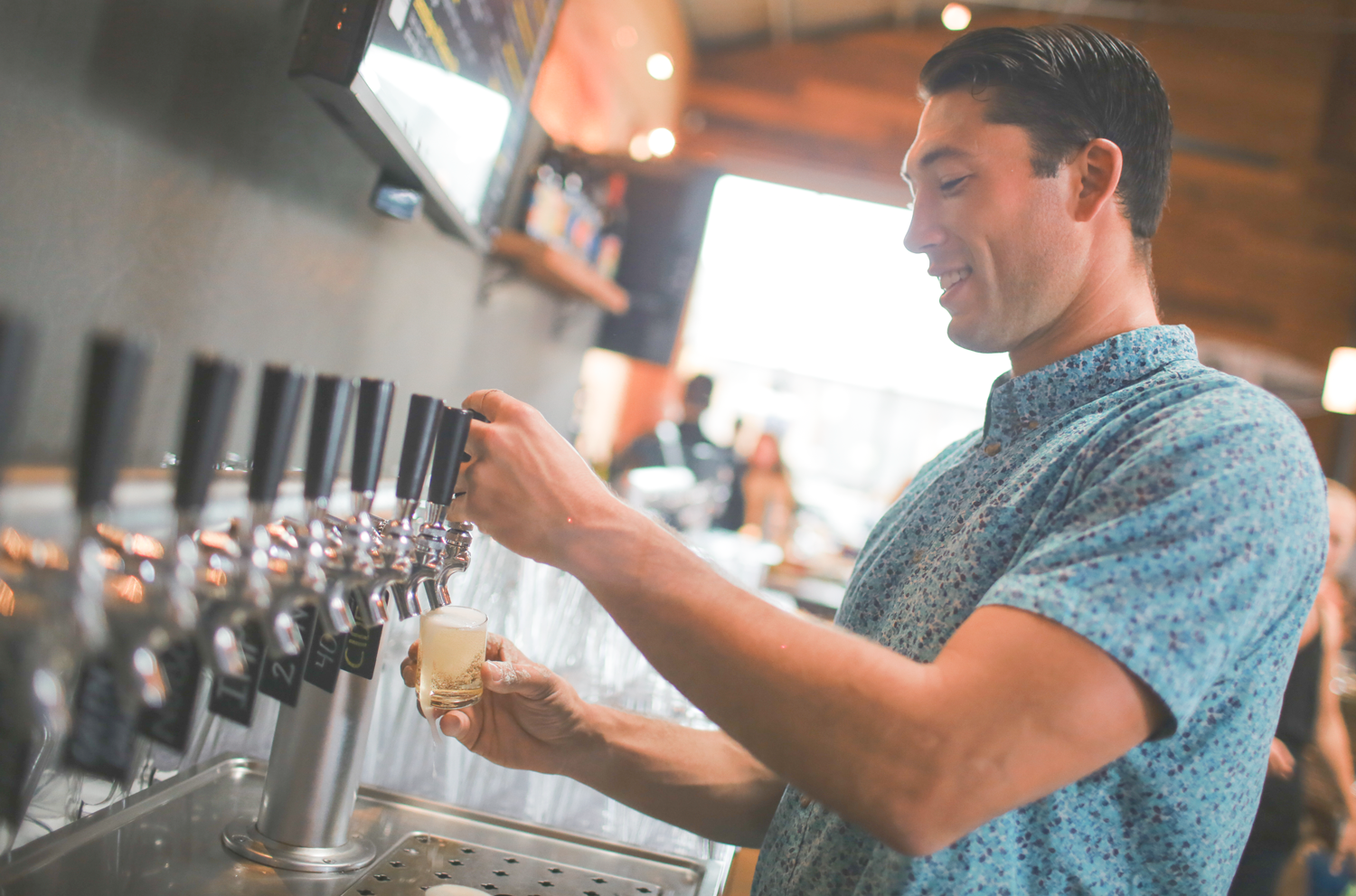 Taylor West pouring a beer at West End Tap & Kitchen, making it look easy.