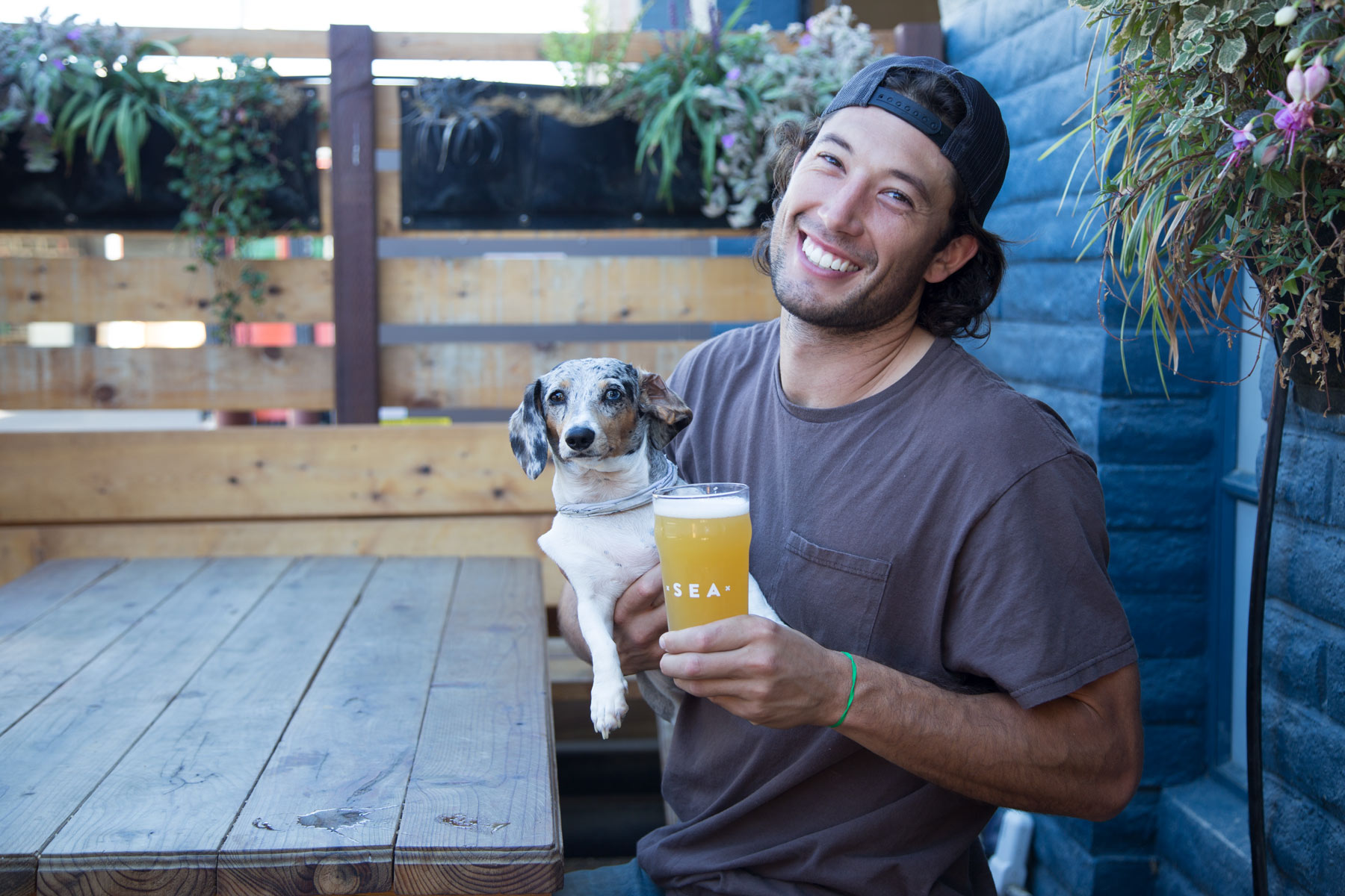 Cofounder Taylor West crushing a new Humble Sea nonic pint glass with Billie the dog.