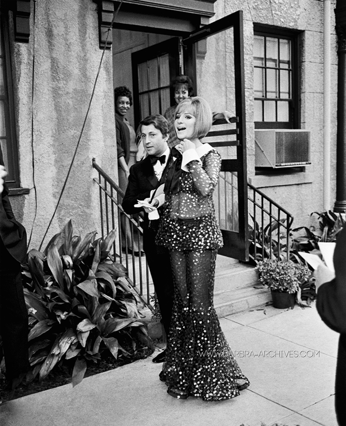 "Arnold Scaasi and Barbra Streisand on the day of the 41st Academy Awards in 1969,  as Streisand wears an ensemble that would soon become iconic. This sheer black sequined overblouse and bellbottom set was worn by Streisand as she won the Oscar for lead actress in ""Funny Girl"".  Image courtesy of Barbra-Archives.com"