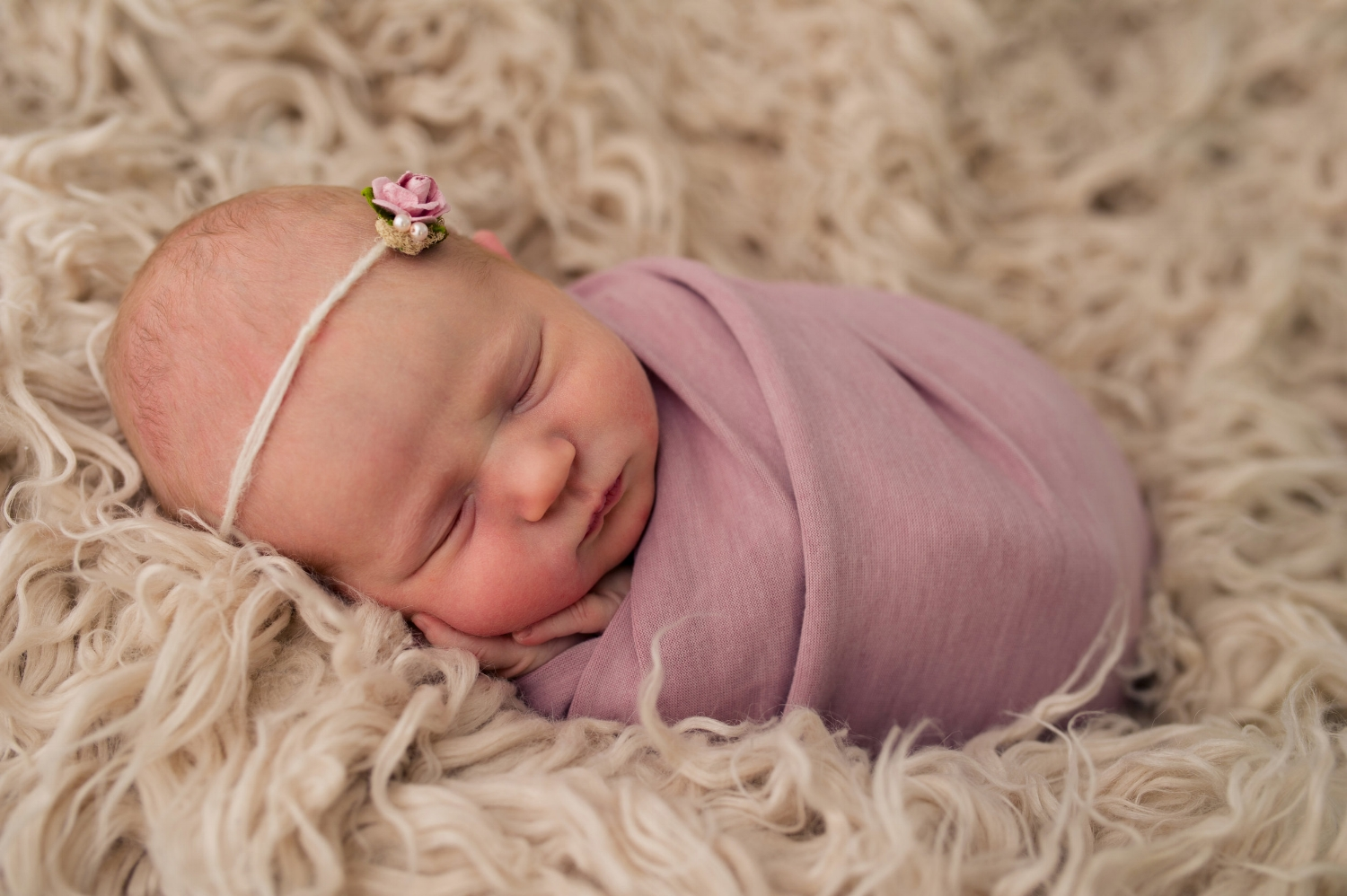 Newborn Baby Girl with Headband and Bundled in Pink