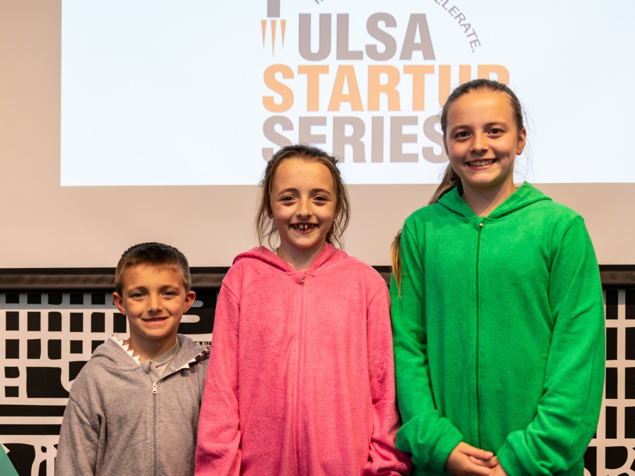 """The children of Angie Myers, founder of My """"Buddy"""" Towel, model the product at the Tulsa Startup Series Live Pitch."""