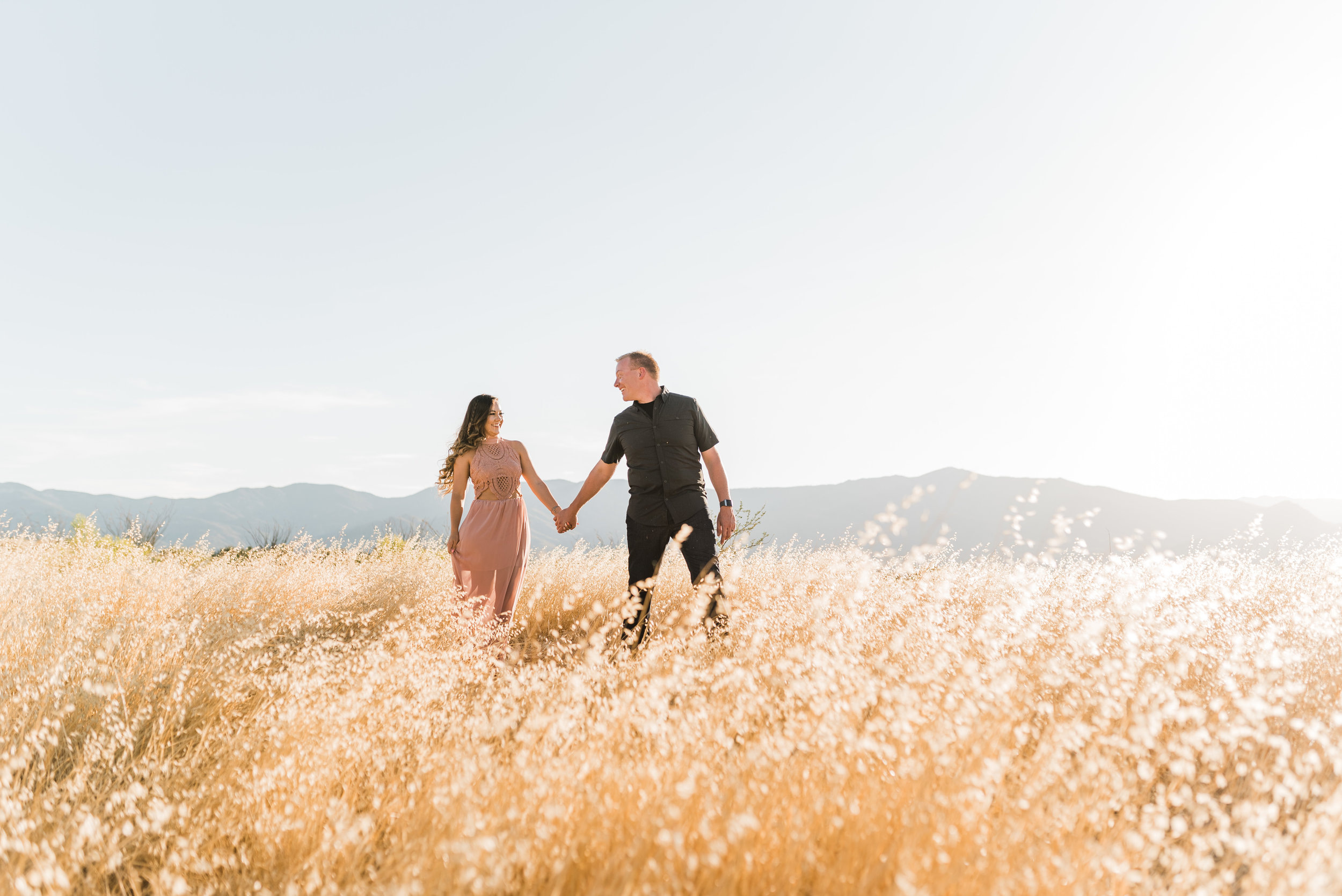 Couple holding hands walking in grass field