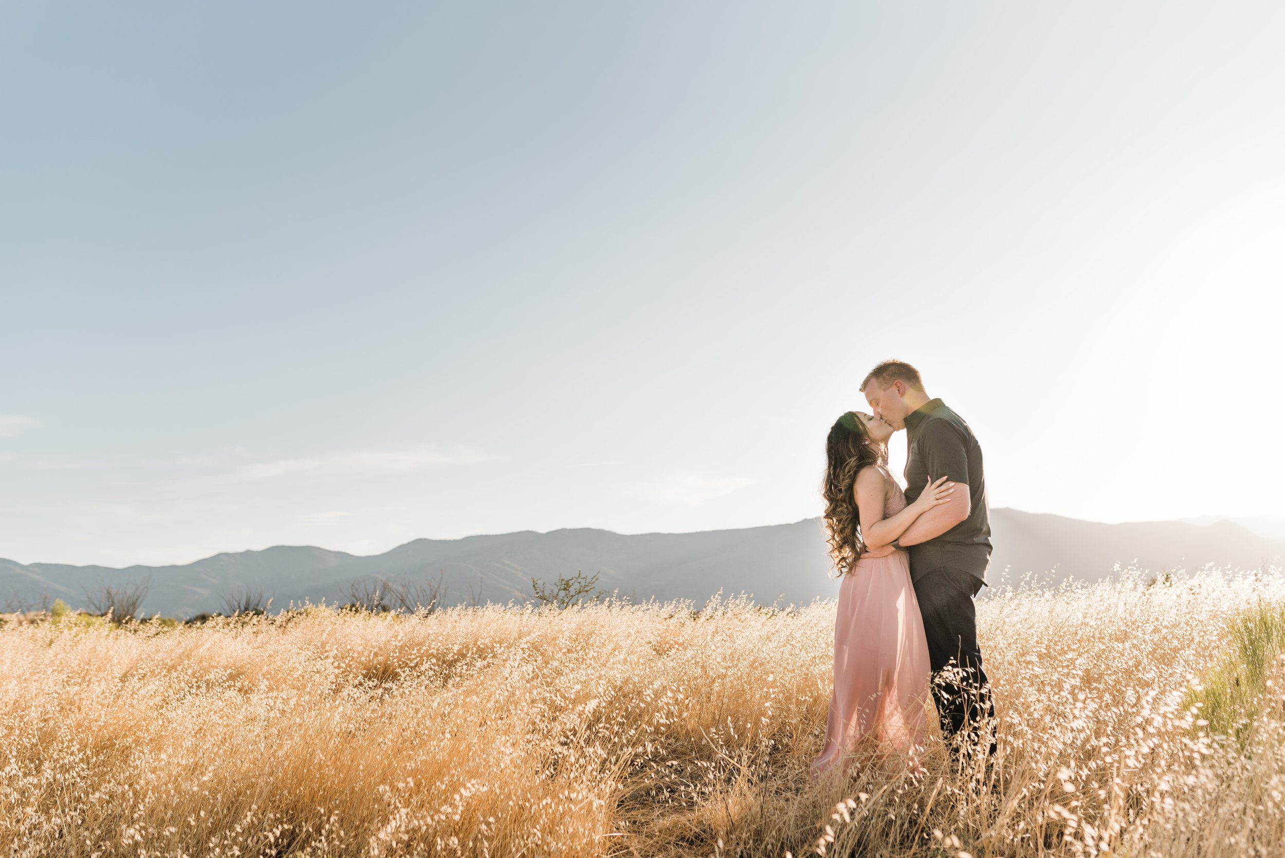 Couple kissing in grass field with sun burst between them