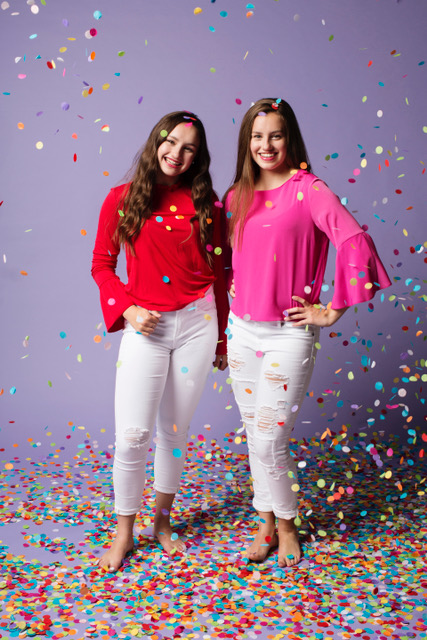 Isabel and Caroline standing with confetti falling down.