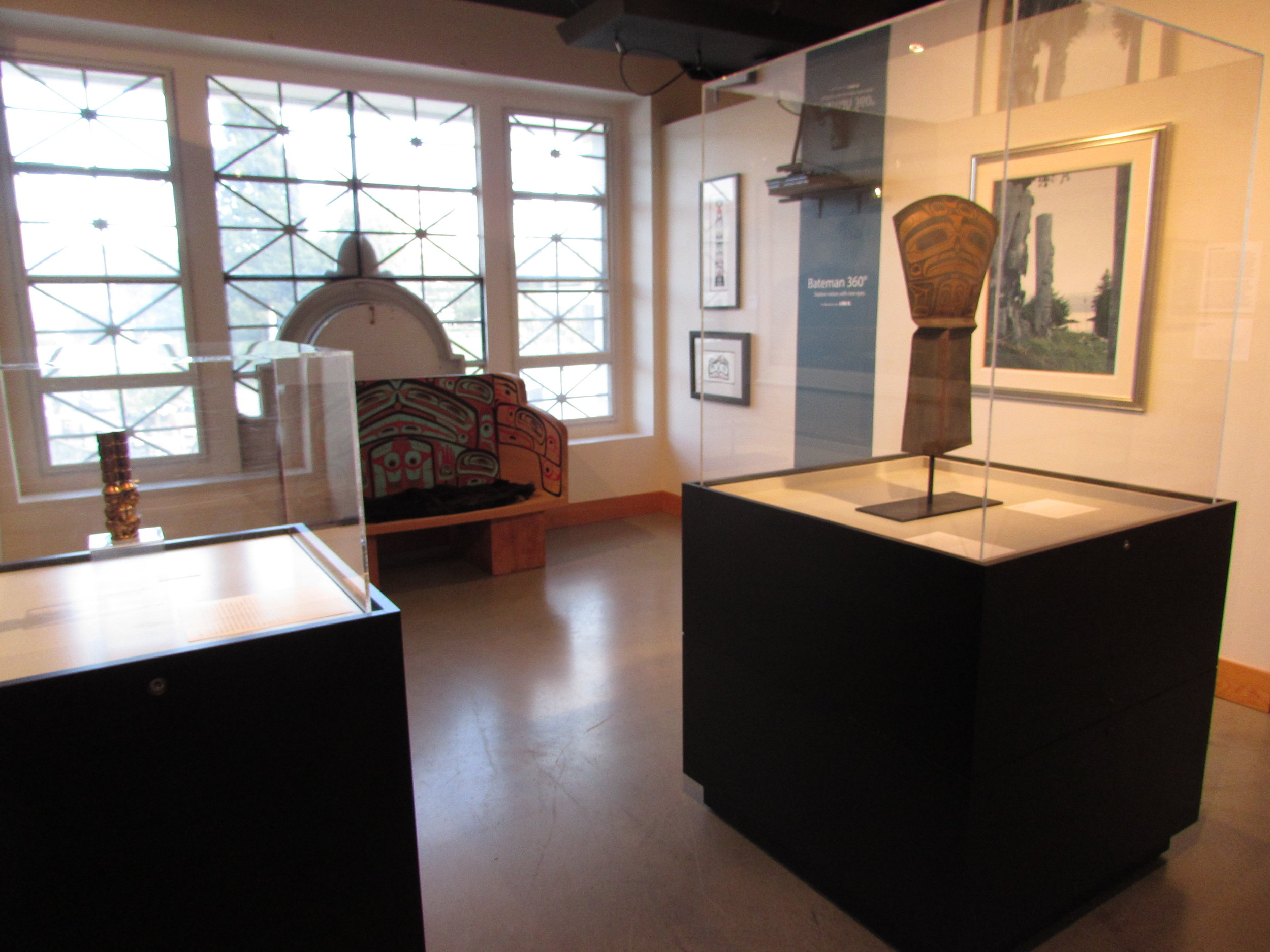 """Jim Hart's """"Three Watchmen"""" maquette (left), bench by Jaalen Edenshaw & Guujaaw (back centre), Jaalen Edenshaw's """"The Wealth Bringer"""" copper shield (right), and W. David Ward's """"Cast in Memory"""" painting (back right)"""