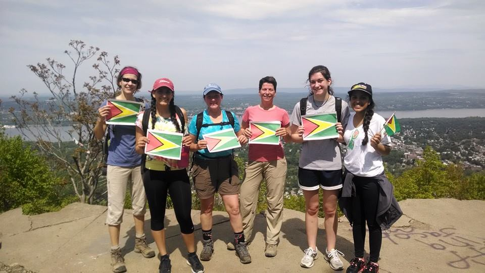 Lori Beer and Maribel Pregnall hike to the top of a mountain in NY (USA) carrying the flag of Guyana (May 26).