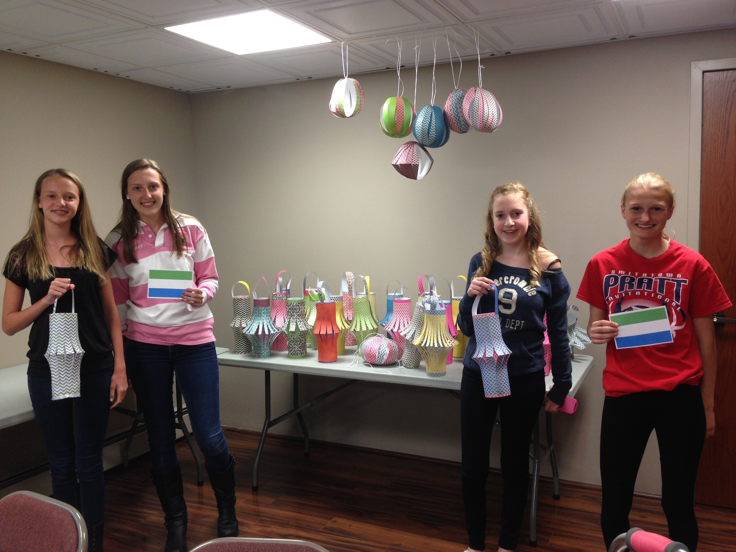 Young women from the USA create traditional paper lanterns for the people of Sierra Leone and hang them outside on Sierra Leone's independence day (April 27).