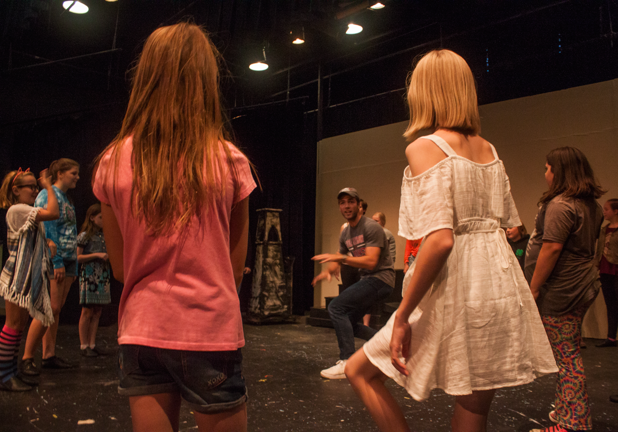 Annabella Harrison (Michael Banks) and Chloe Cranch (Jane Banks) look on as Director, Ty Molbak works choreography with the Chimney Sweeps for Step in Time. Photo by Kathryn Lynn Morgen