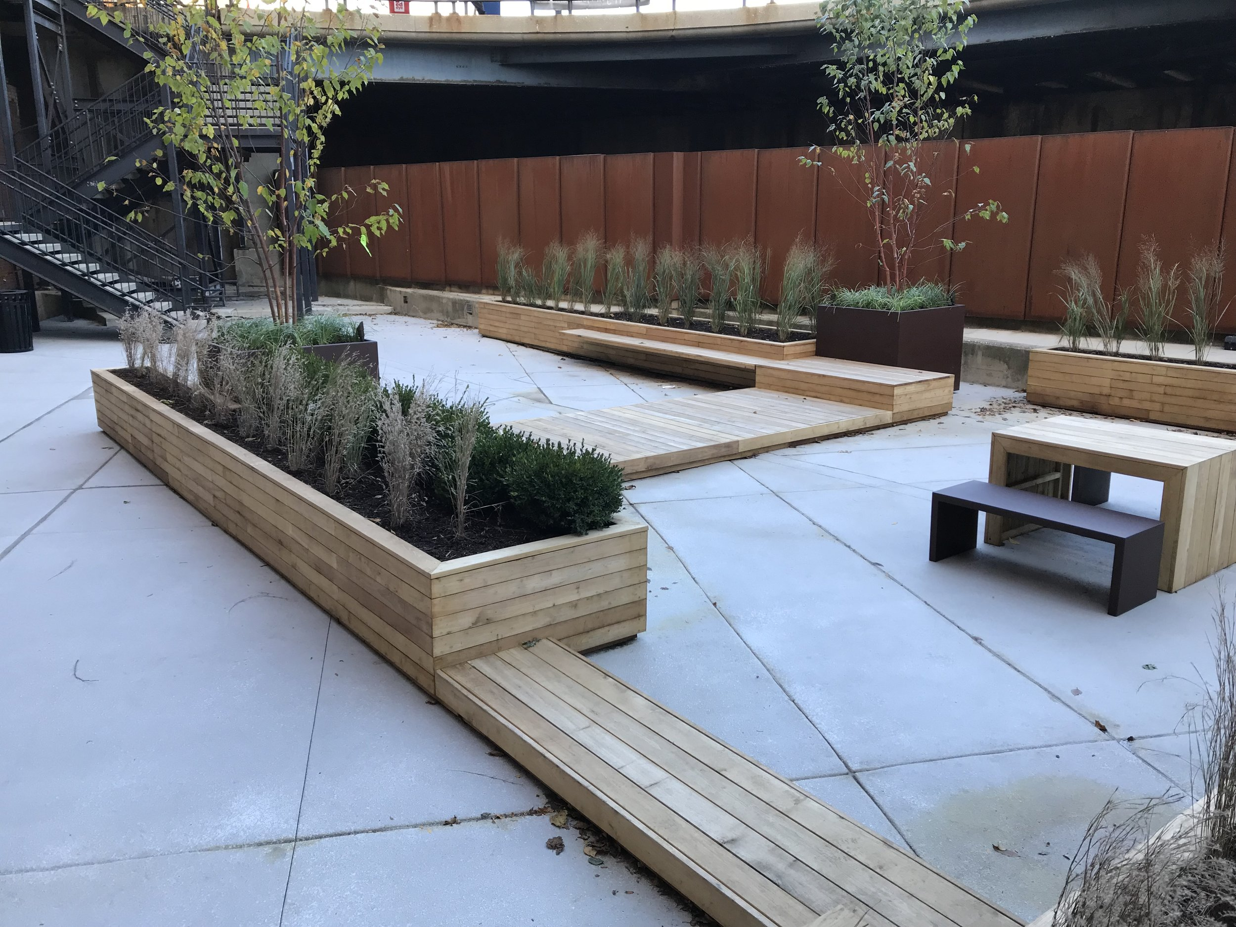 Commercial Courtyard - Long planters, deck panels, benches and tables made from sustainable black locust wood. The wood is Select & Better grade, kiln dried and left unfinished to weather grey.