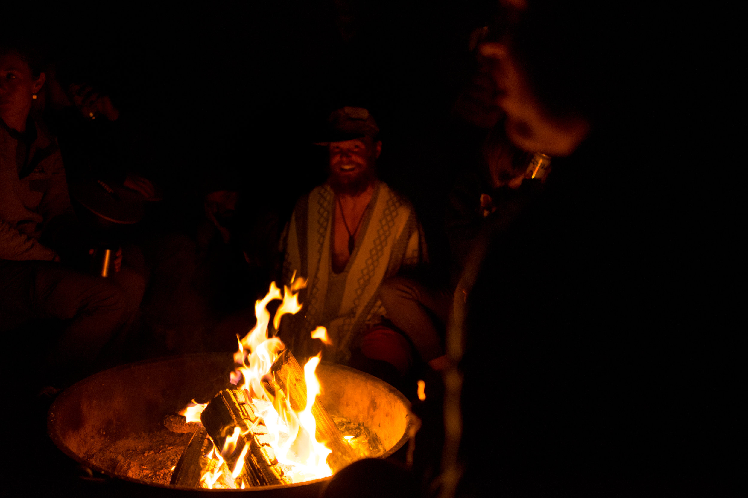 Climbers surround the campfire at Camp #5, where climbers have been coming to share creative and often low-budget group-made dinners, and afterwards drink and socialize into the night.