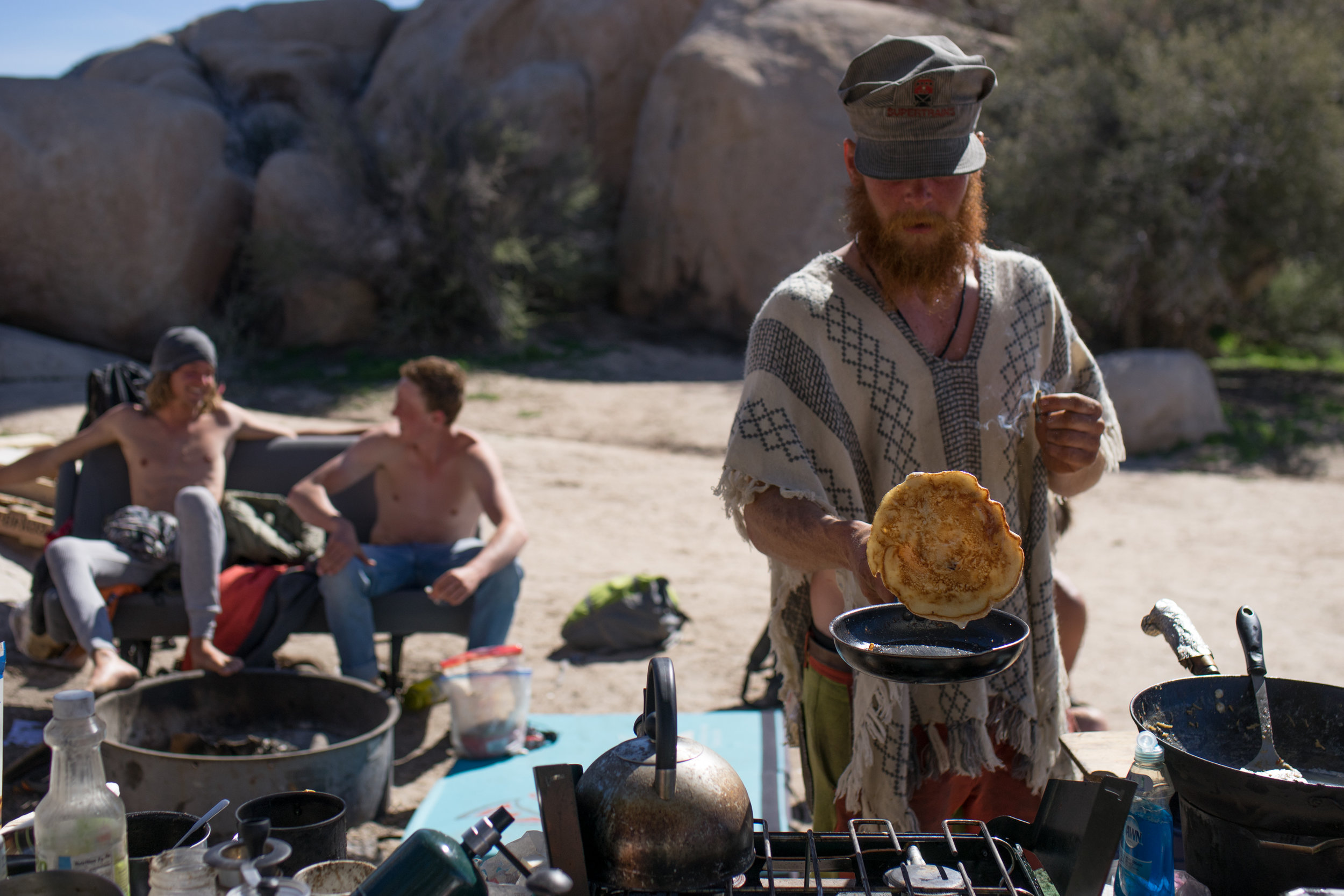 A climber cooks breakfast from the previous night's leftovers, while climbers from other campsites socialize around the campfire.