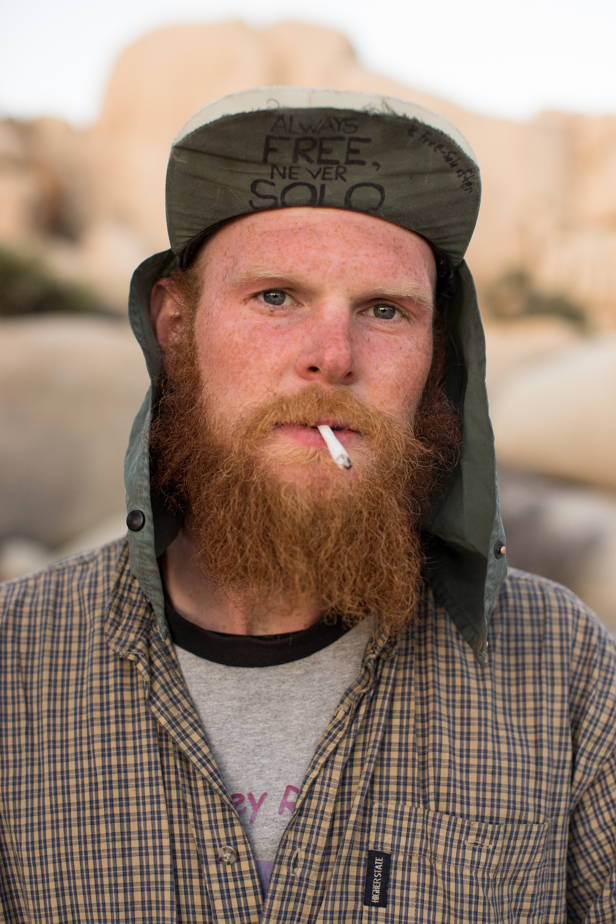 "Evan ""Red Beard"", 27, has been unemployed since July, when he last worked as an industrial pipe fitter. Since coming to Joshua Tree last December, he has worn out his only pair of shoes, and now walks around barefoot. He traveled to the park alone, and with $400 to his name, he remains relaxed, upbeat, and extremely carefree."