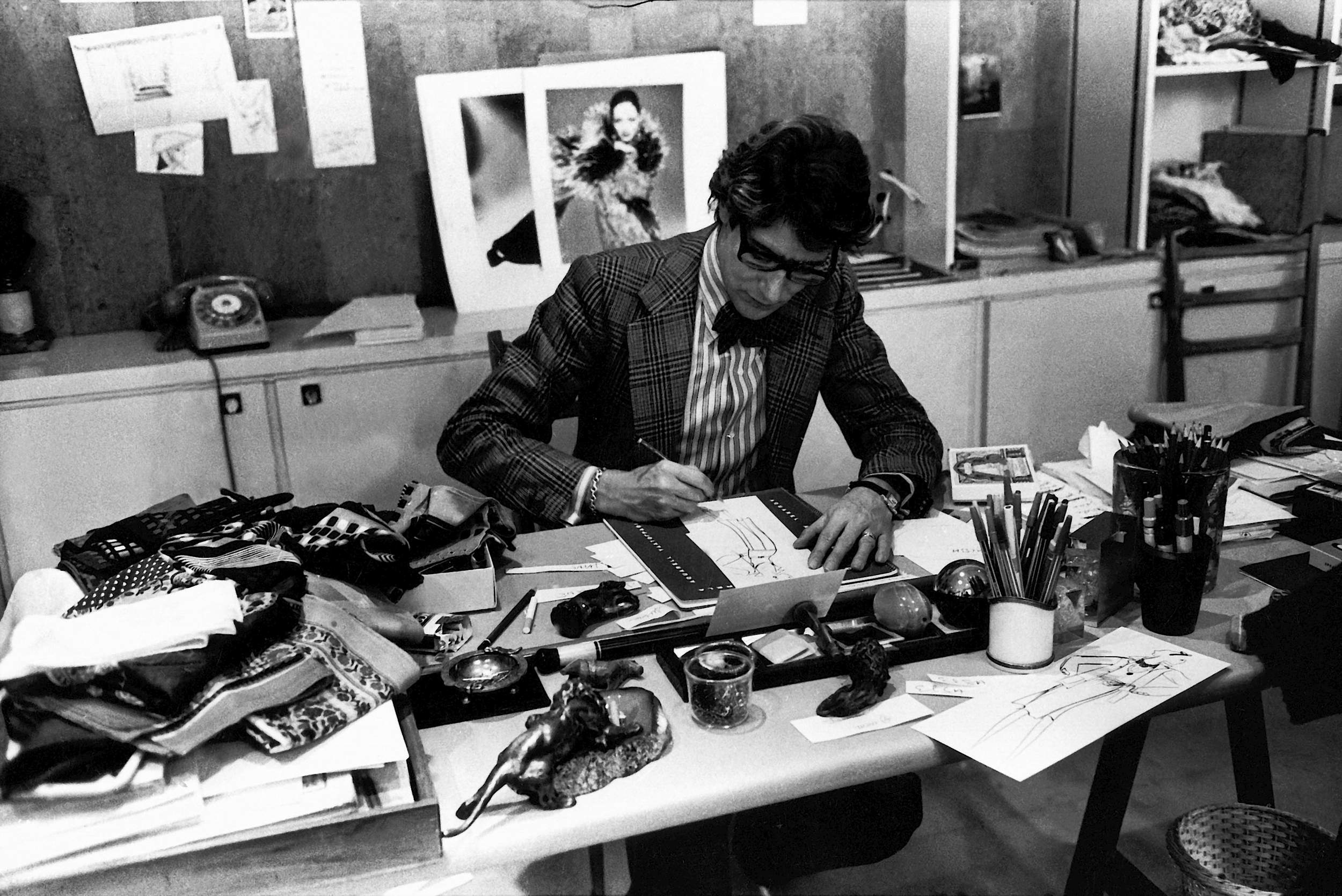 The couturier at work in 1976 in his studio 5 avenue Marceau, Paris. © Fondation Pierre Bergé – Yves Saint Laurent, Paris / Guy Marineau.