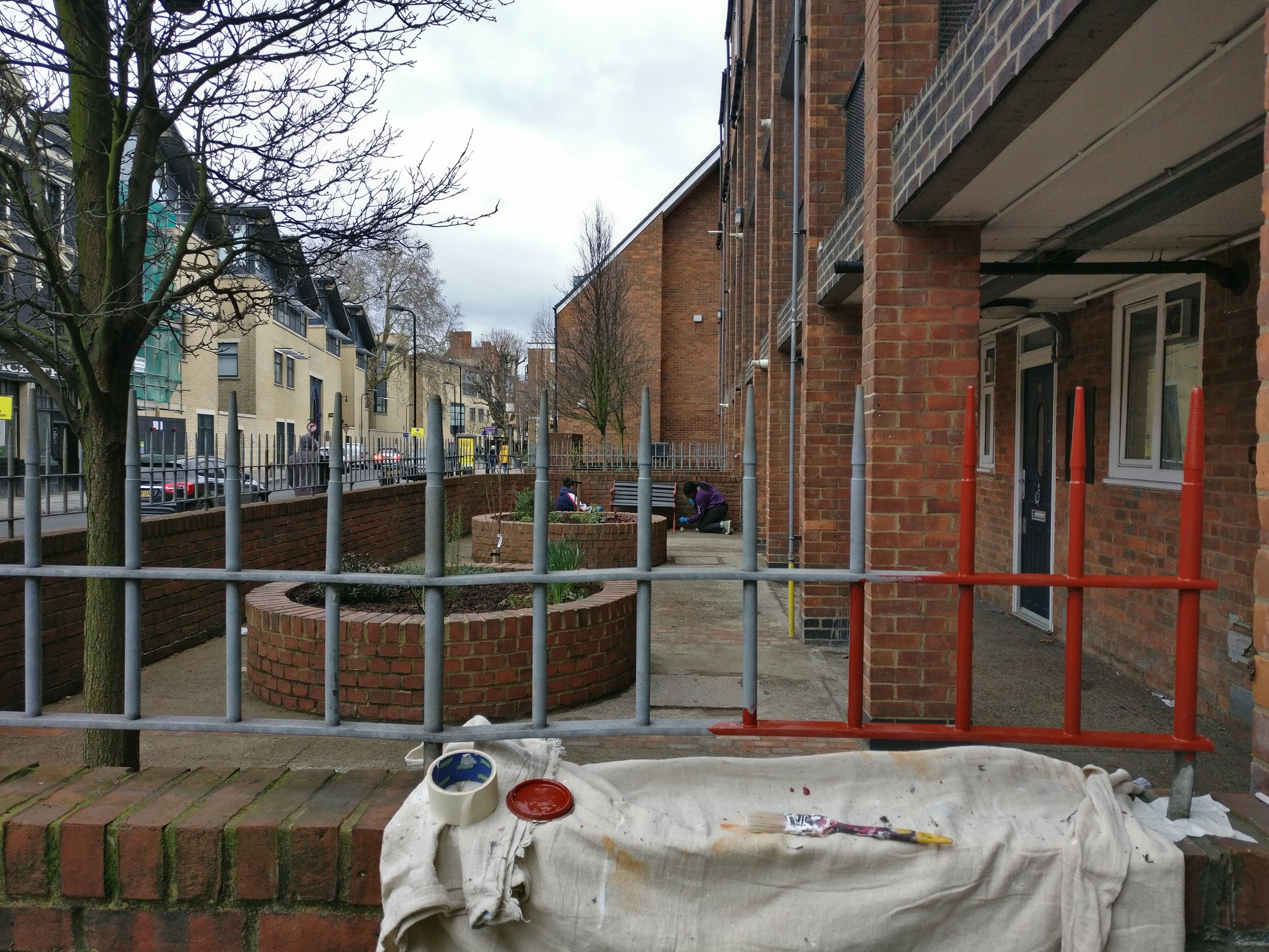 Renewing dull grey railings with red oxide paint to match the benches