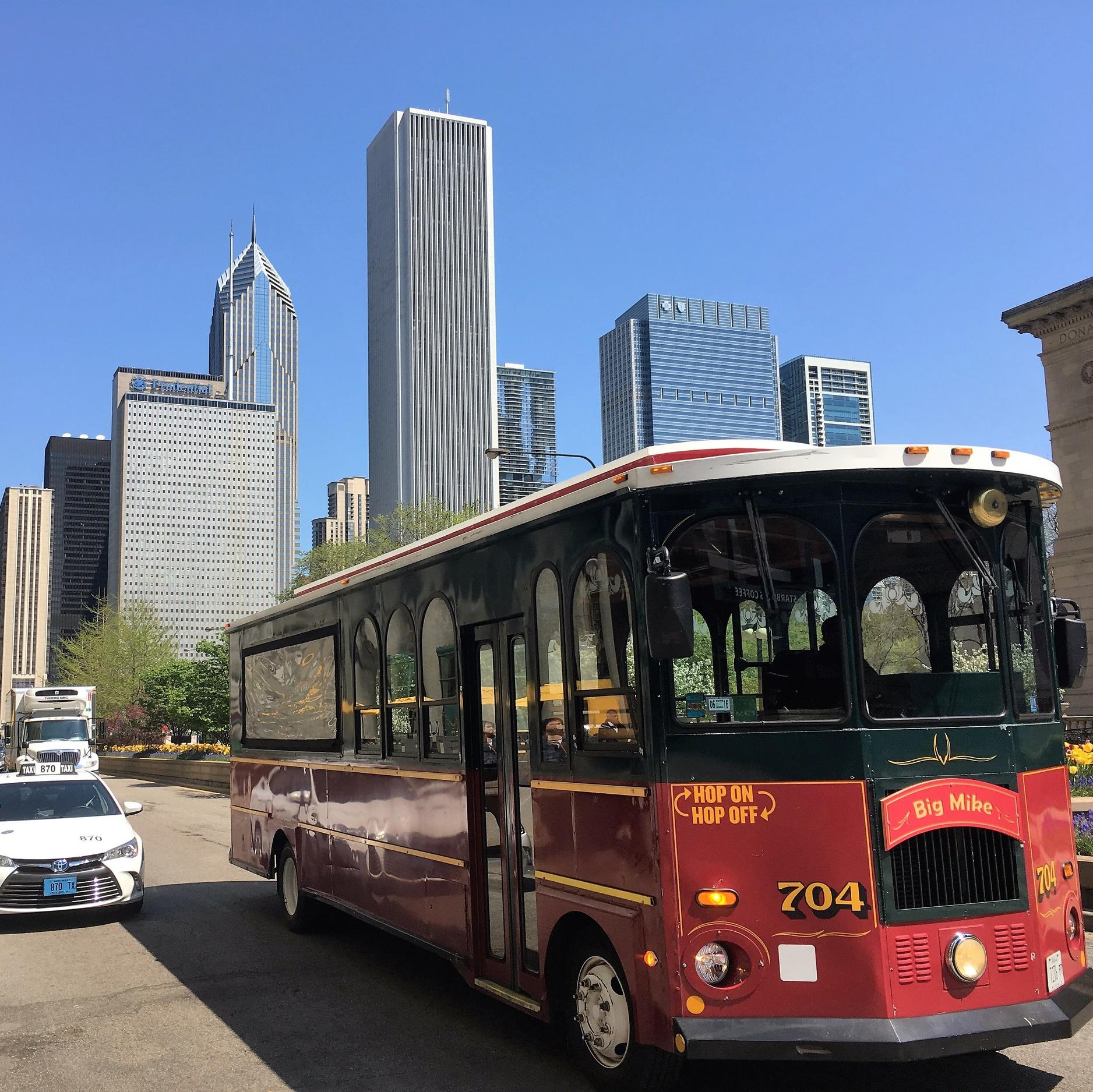 Paikallisbussi ja pilvenpiirtäjijä taustalla