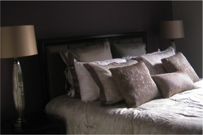 Plum wall color and champagne bedding with mercury glass bedside lamps