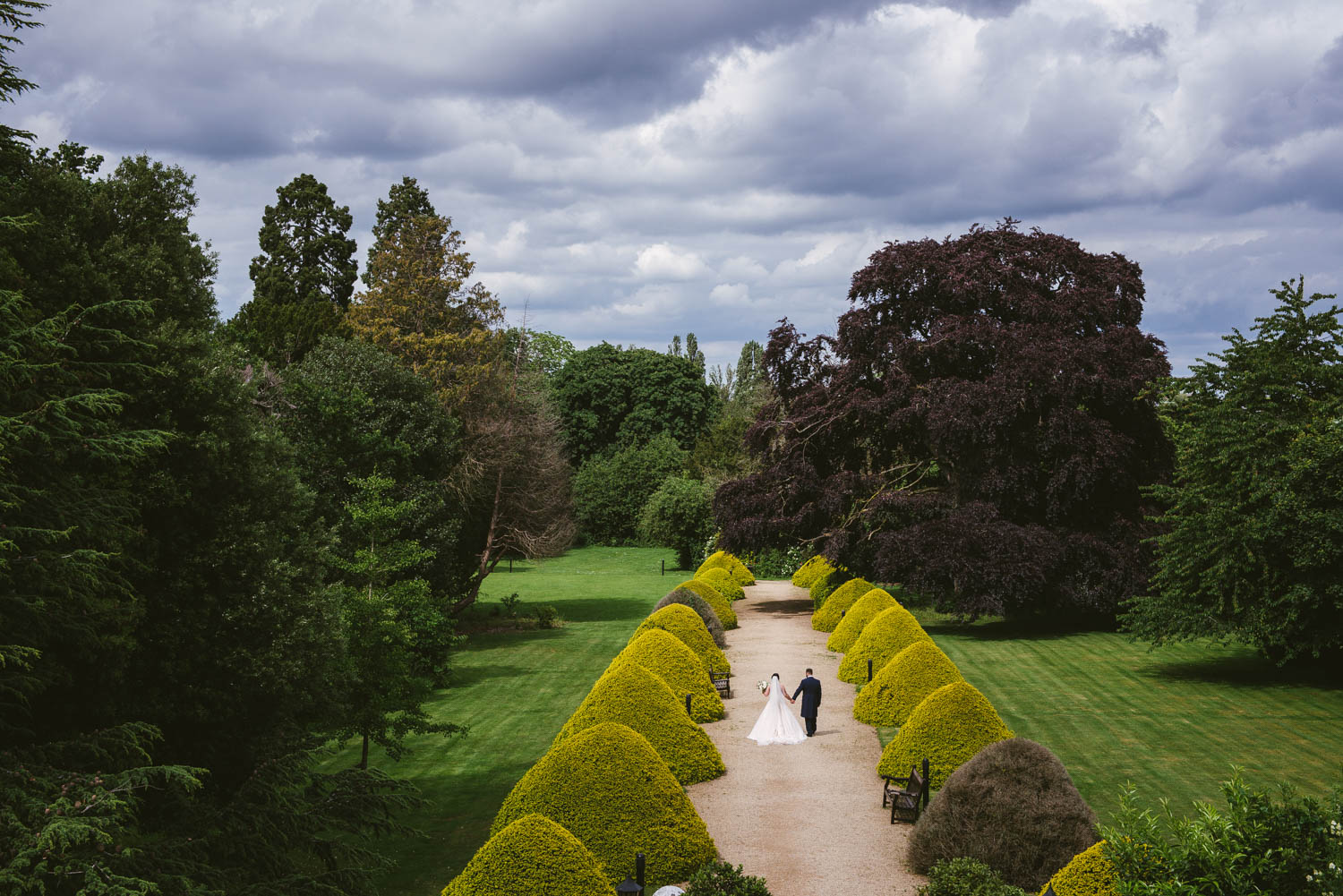 bride and groom stroll hand in hand at manor by the lake, cotswolds, cheltenham
