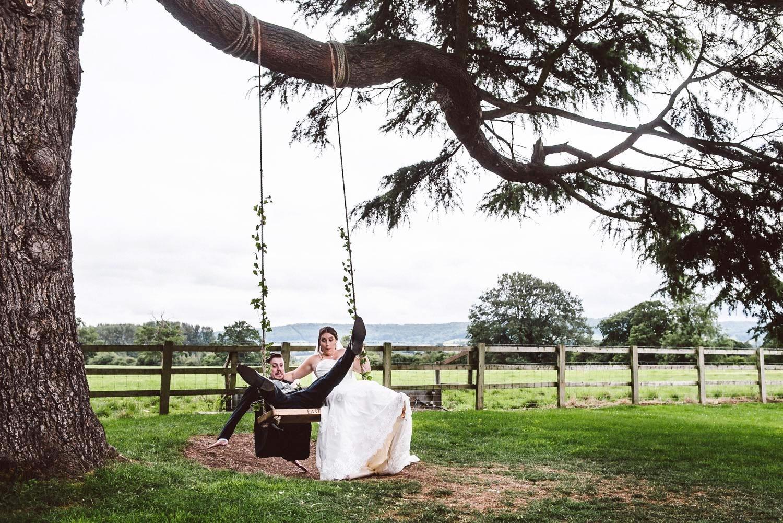 Groom falling off a swing - documentary wedding, cotswolds