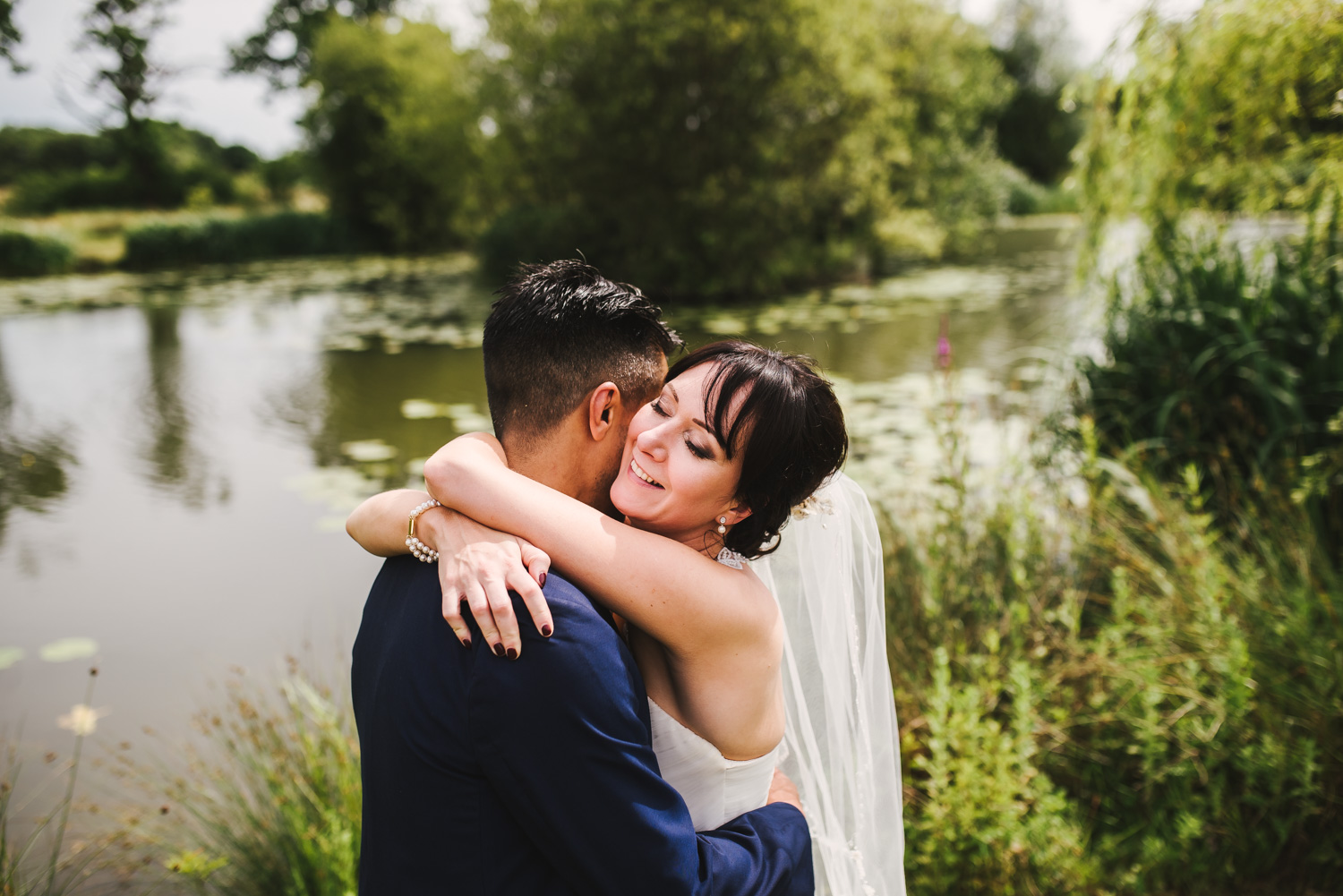 bride-hugs-groom-by-the-lake.jpg