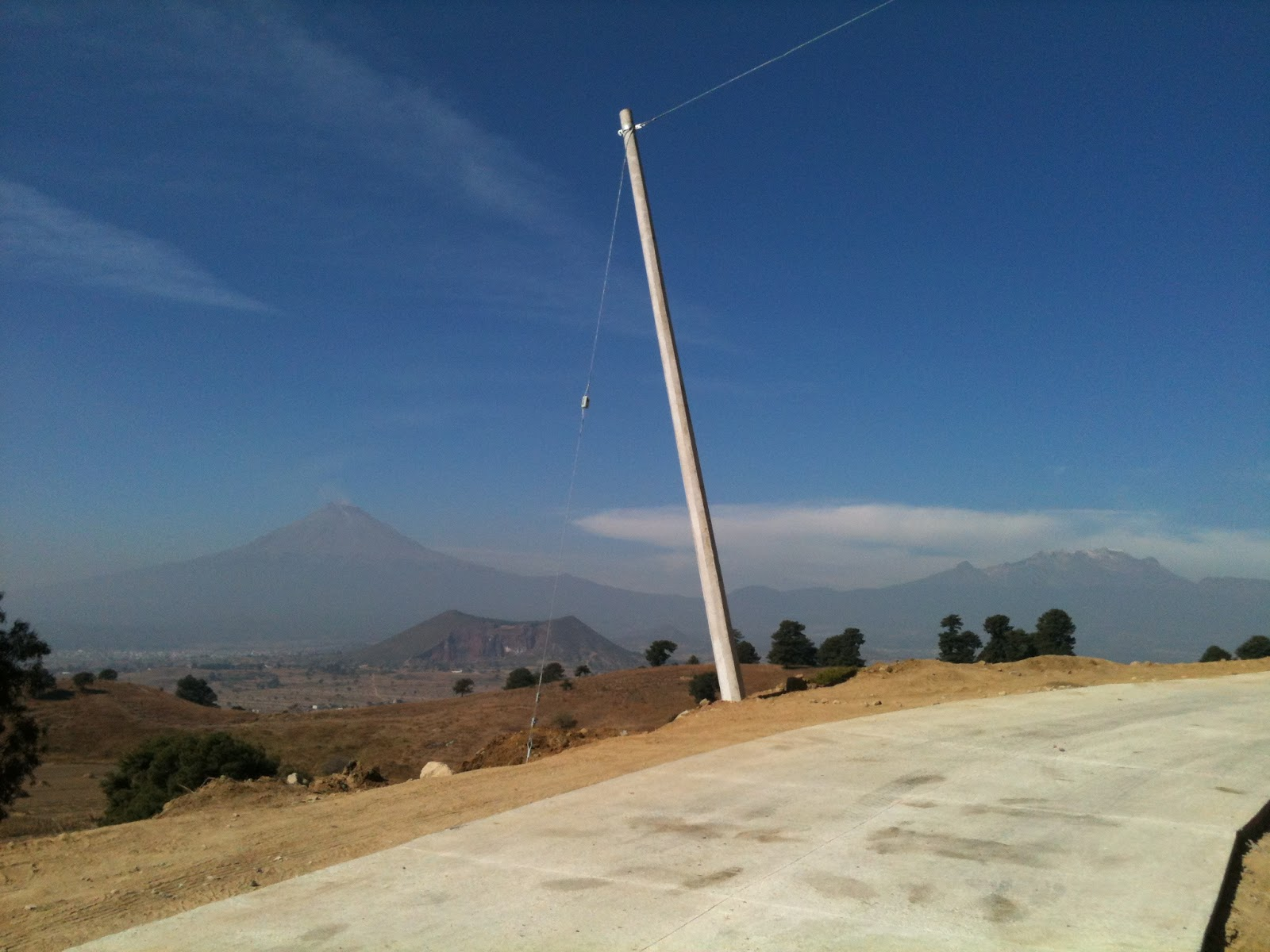 La hermosa vista de los volcanes con pavimento y postes chuecos