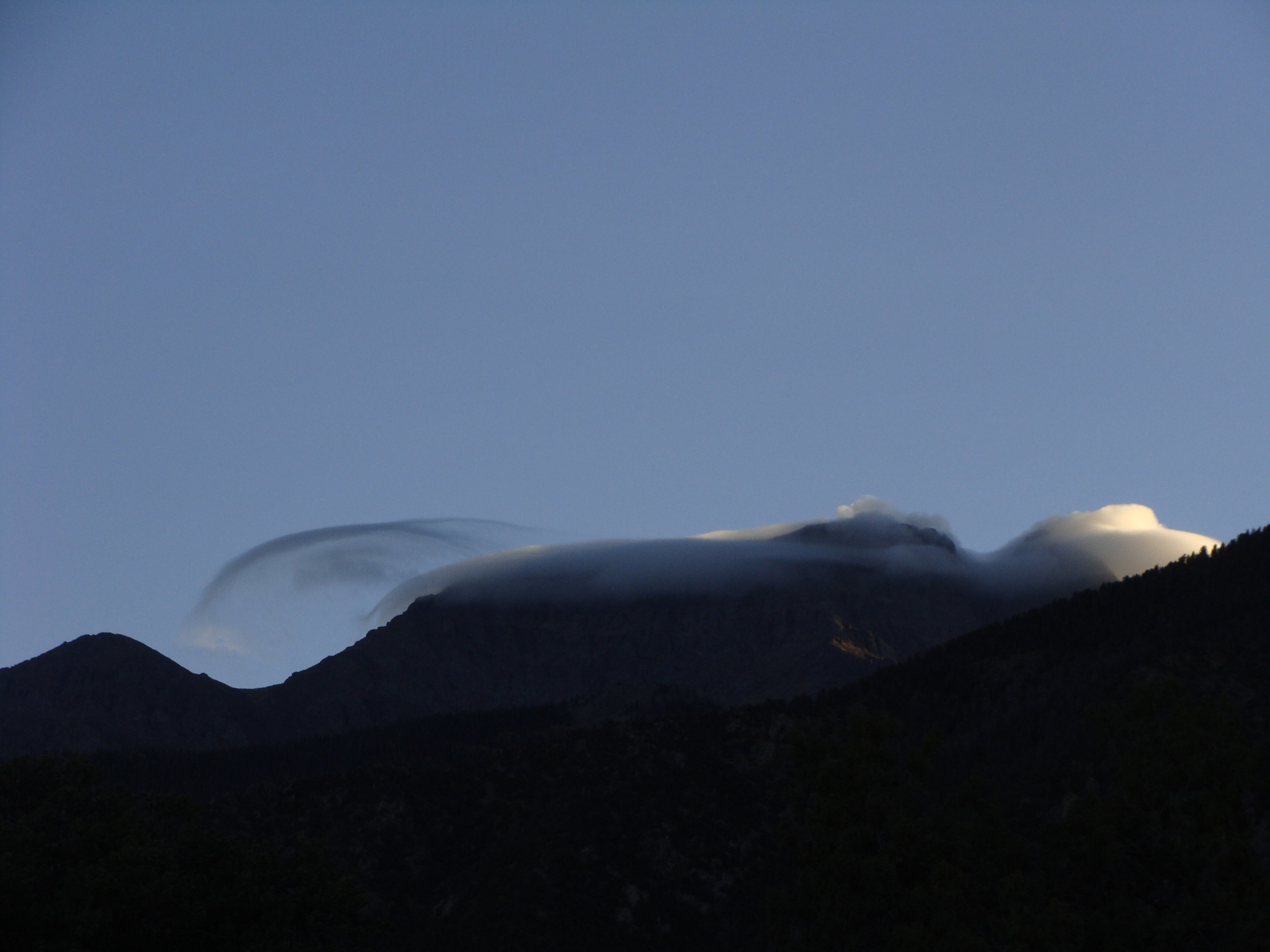 A morning cloud cap as the sun hits the mountains