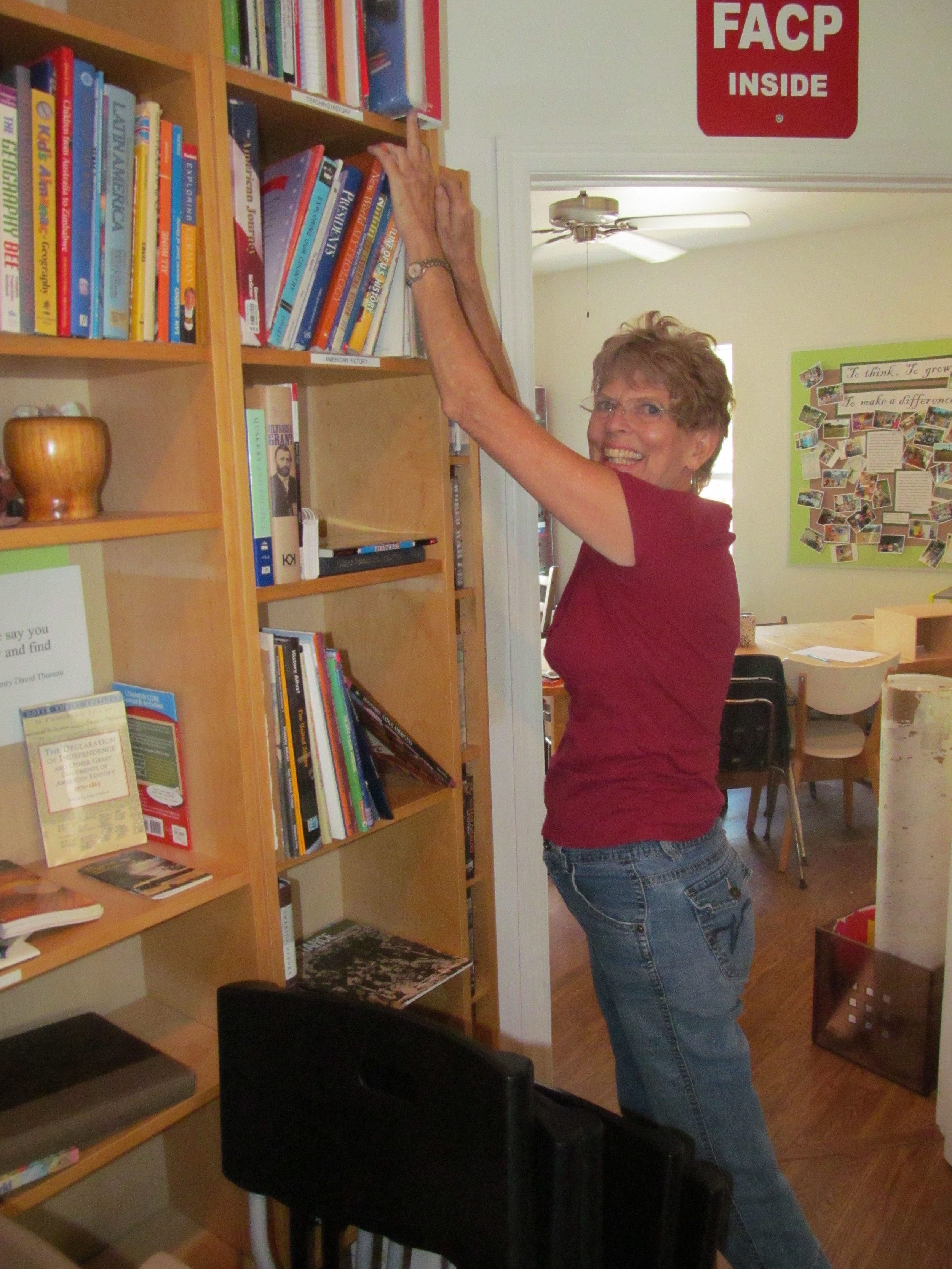 Dr. Barbara Carson, Community advisor, helps with shelving resources.