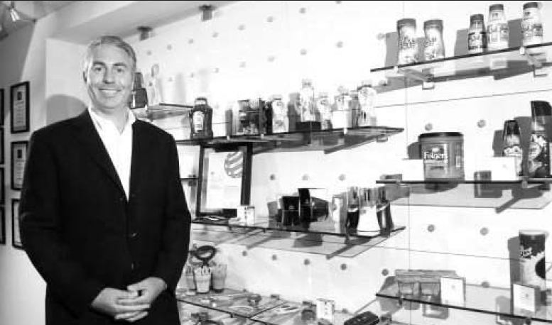 Peter Clarke, founder and CEO of Product Ventures, headquartered in Fairfield, poses with a display of various products the company has designed for companies like Heinz, Folgers and Similac.  Clarke's company is celebrating its 15th anniversary