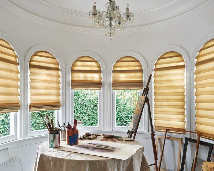 Hunter Douglas Vignette Modern Roman Shades are available as a specialty window covering.  The arched portion of the window is fixed/stationary with a divider rail that allows the bottom of the shade to function.