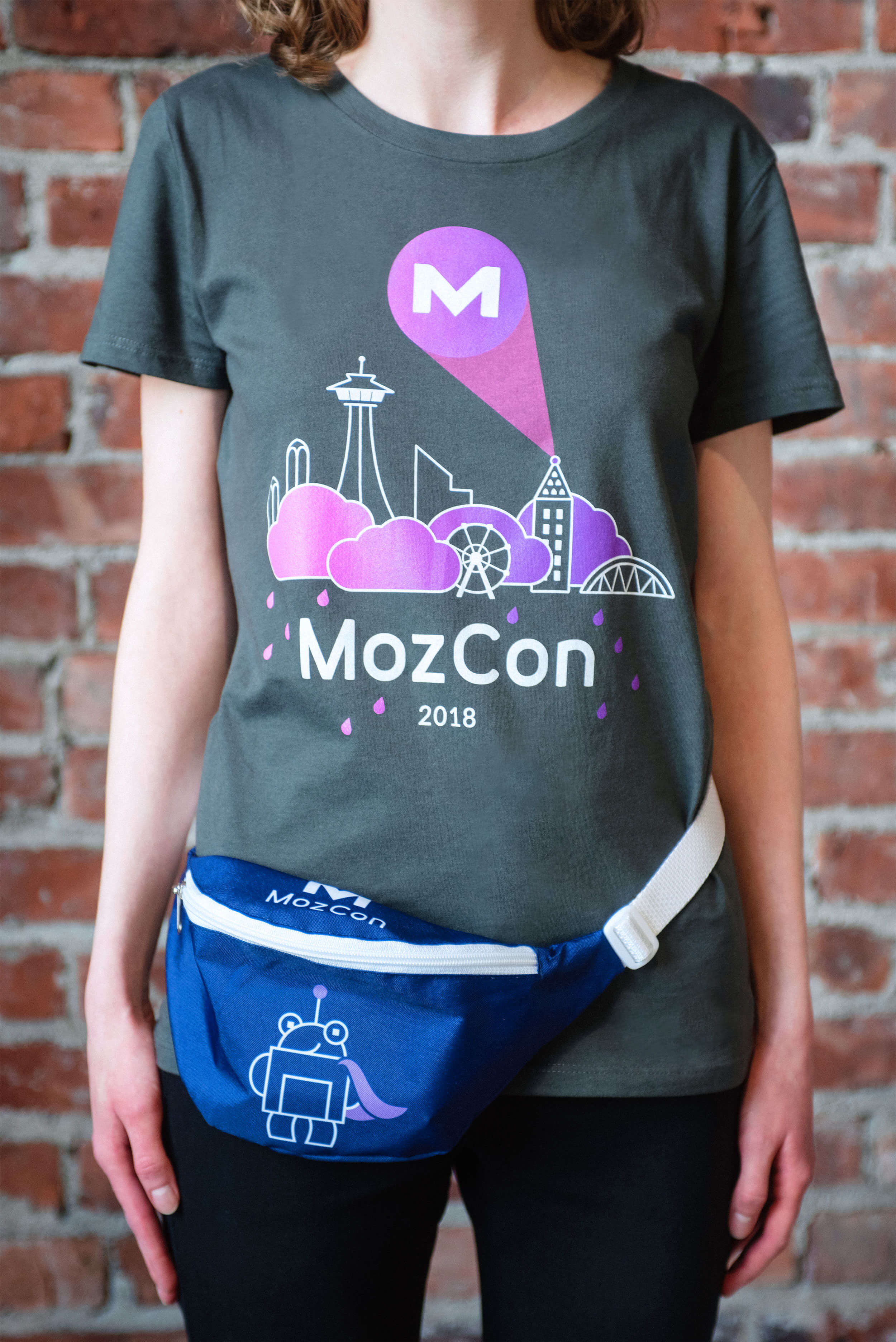 MozCon 2018 swag: Mozopolis cityscape graphic tee featuring the Roger signal (AKA the MozCon logo) projected from the illustrated Smith Tower, and purple Super Roger fanny pack.