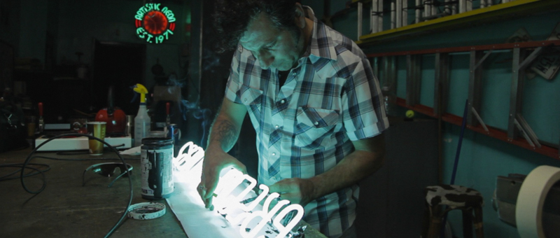 Robbie finishing a neon sign in his shop