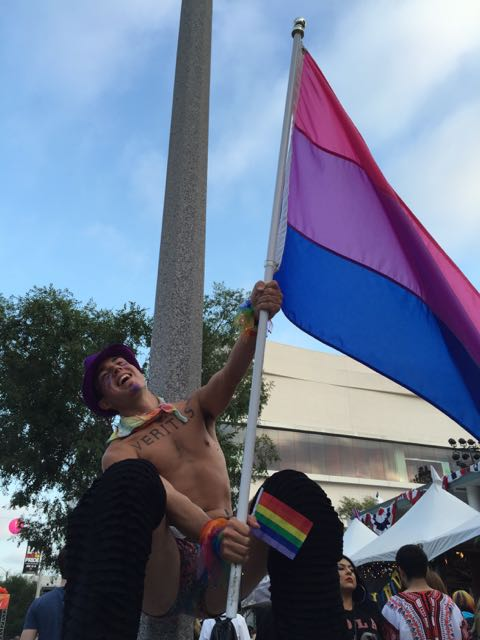 Nathaniel from amBi SD promoting the bisexual.org booth on stilts at the festival!