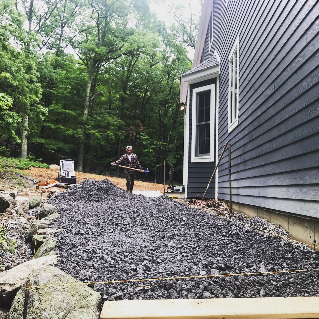 Spreading crushed gravel and sand mix (Item #4) as a base for the patio