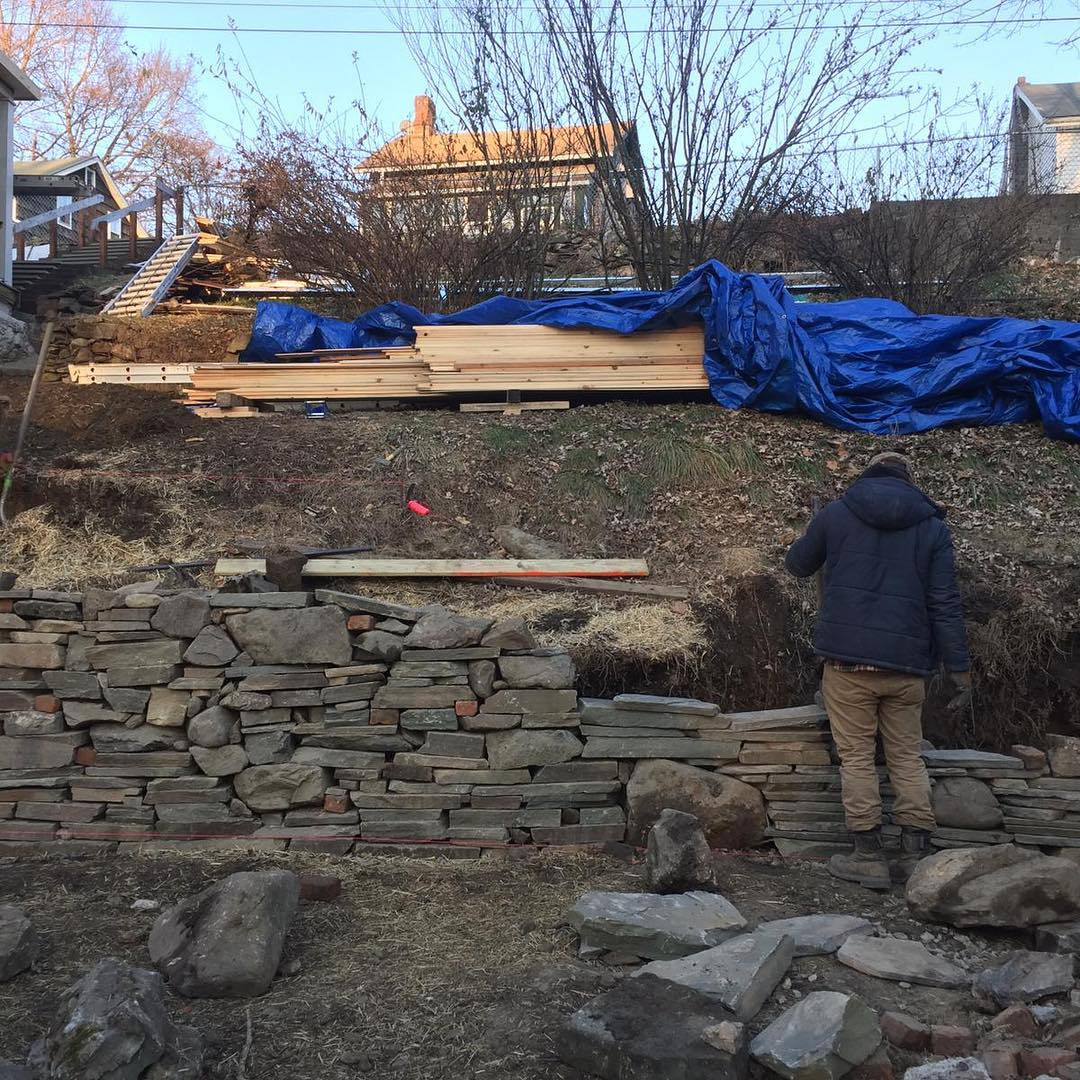 Rebuilding a stone retaining wall with both new and recycled stone