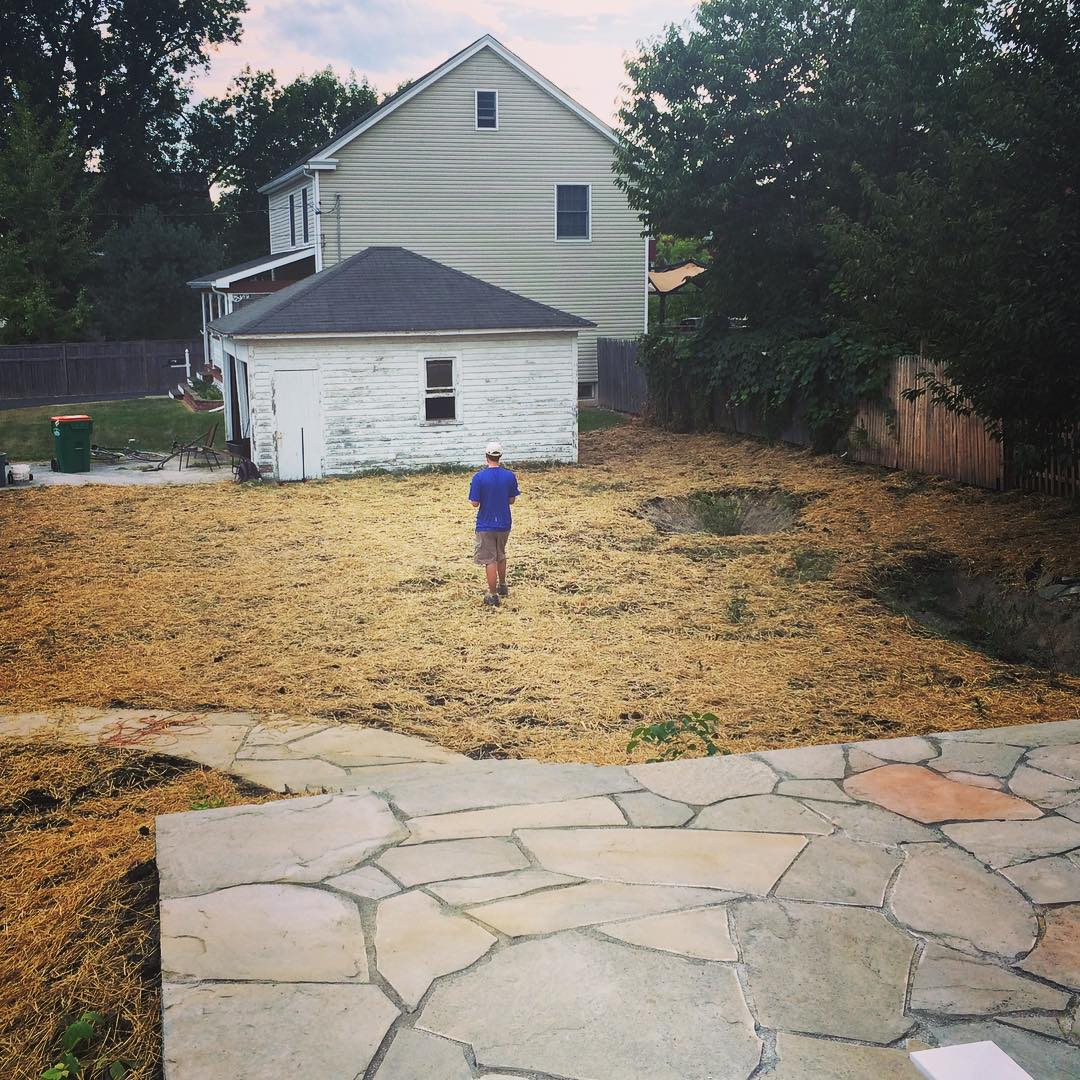 Fresh soil is covered in seed and straw at the end of a residential design/build