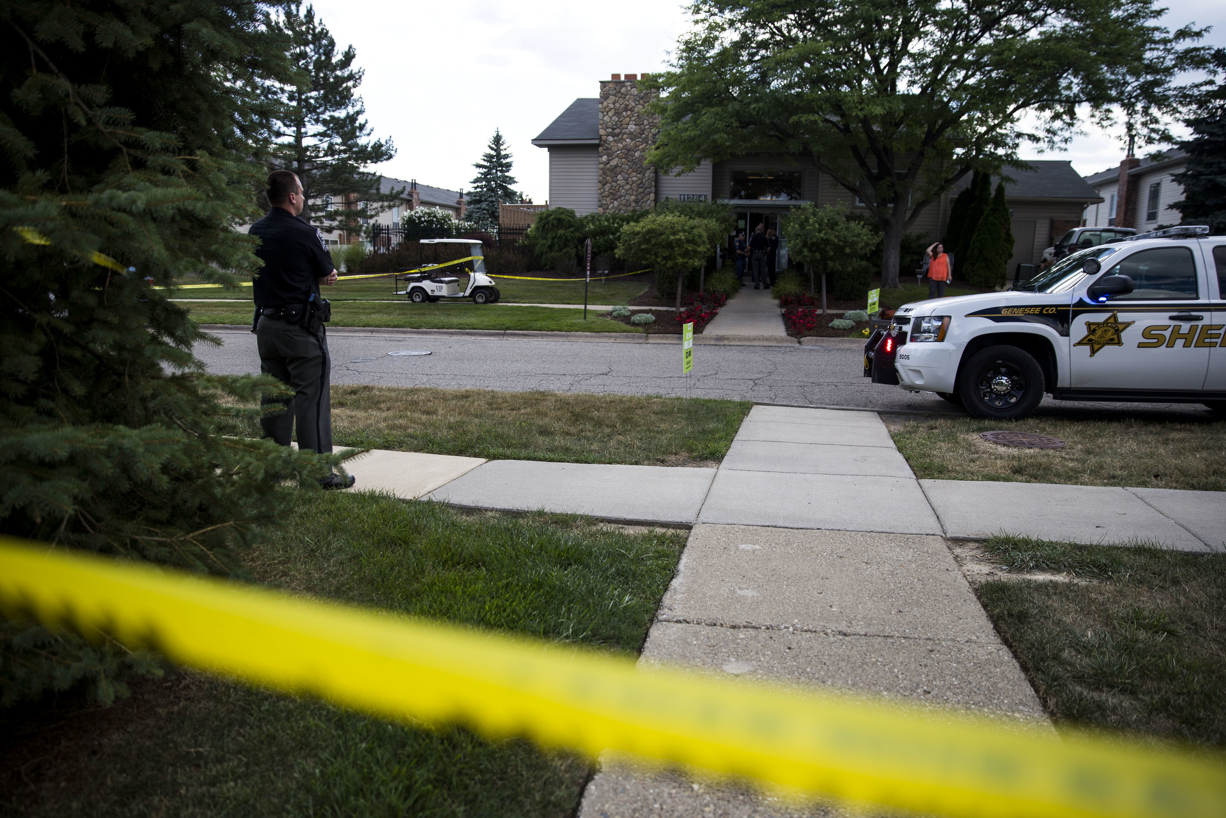 Officers investigate a crime screen after a shooting at Grand Oak Apartments in Grand Blanc on Tuesday, July 26, 2016.
