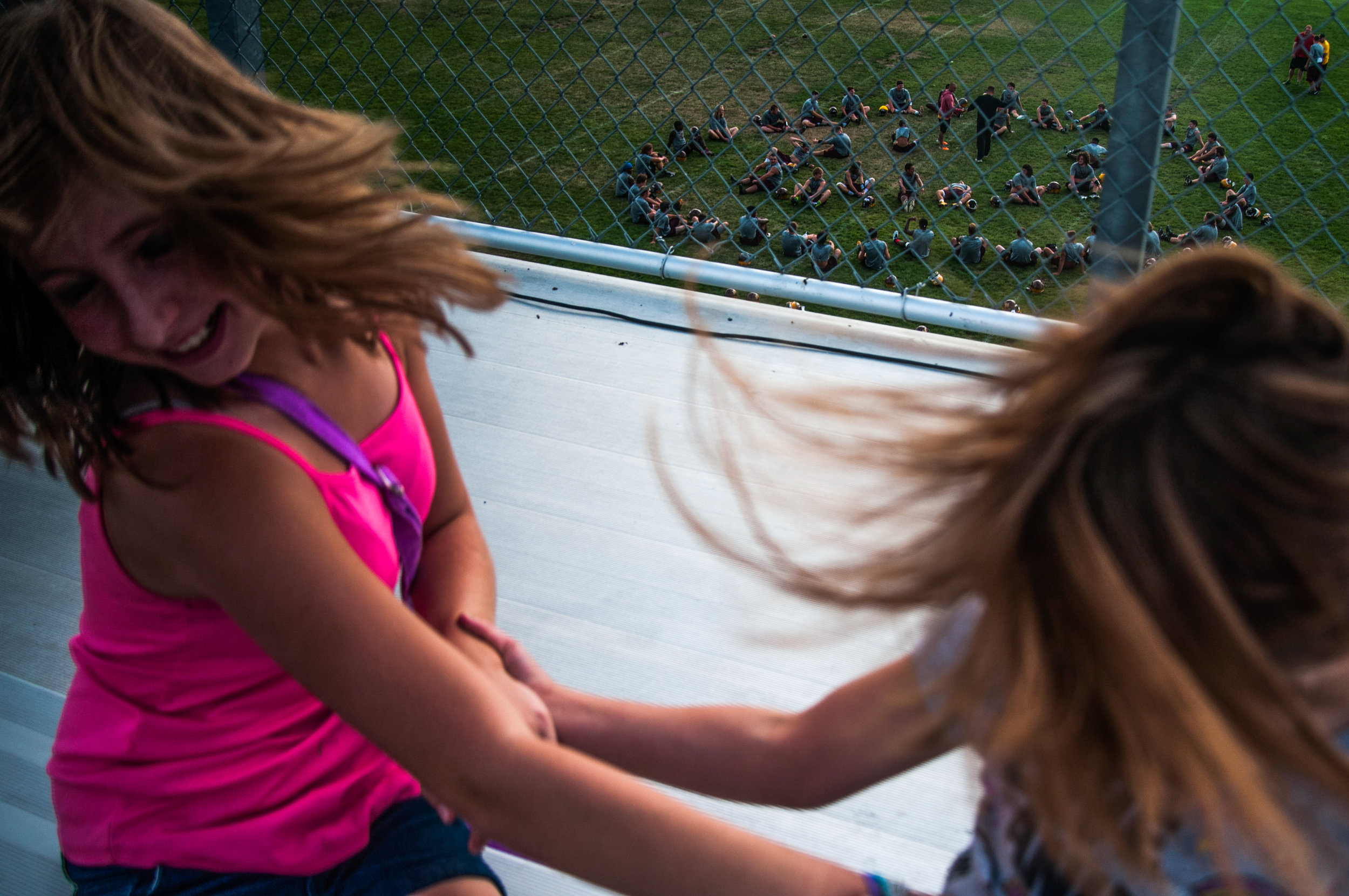 From left, Aneisa Krueger, 11, and Angel Stocklell, 8, both of Davison, toss their hair while playing together during the Davison Community Schools Back to School Blast on Tuesday, August 9, 2016 at Cardinal Stadium in Davison.