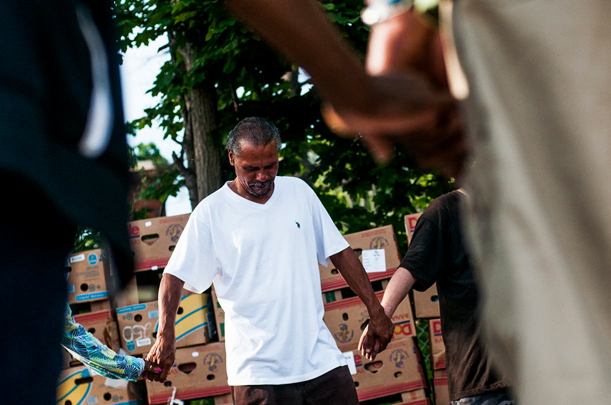 Mike Langford prays over the food before the Christ Enrichment Community's Food Give Away on Friday, August 5, 2016 at Shiloh Missionary Baptist Church in Flint. Every Friday morning around 9 a.m., Christ Enrichment Community and its partners distribute fresh fruits, vegetables, baked goods, hygiene products and other necessities to the community.