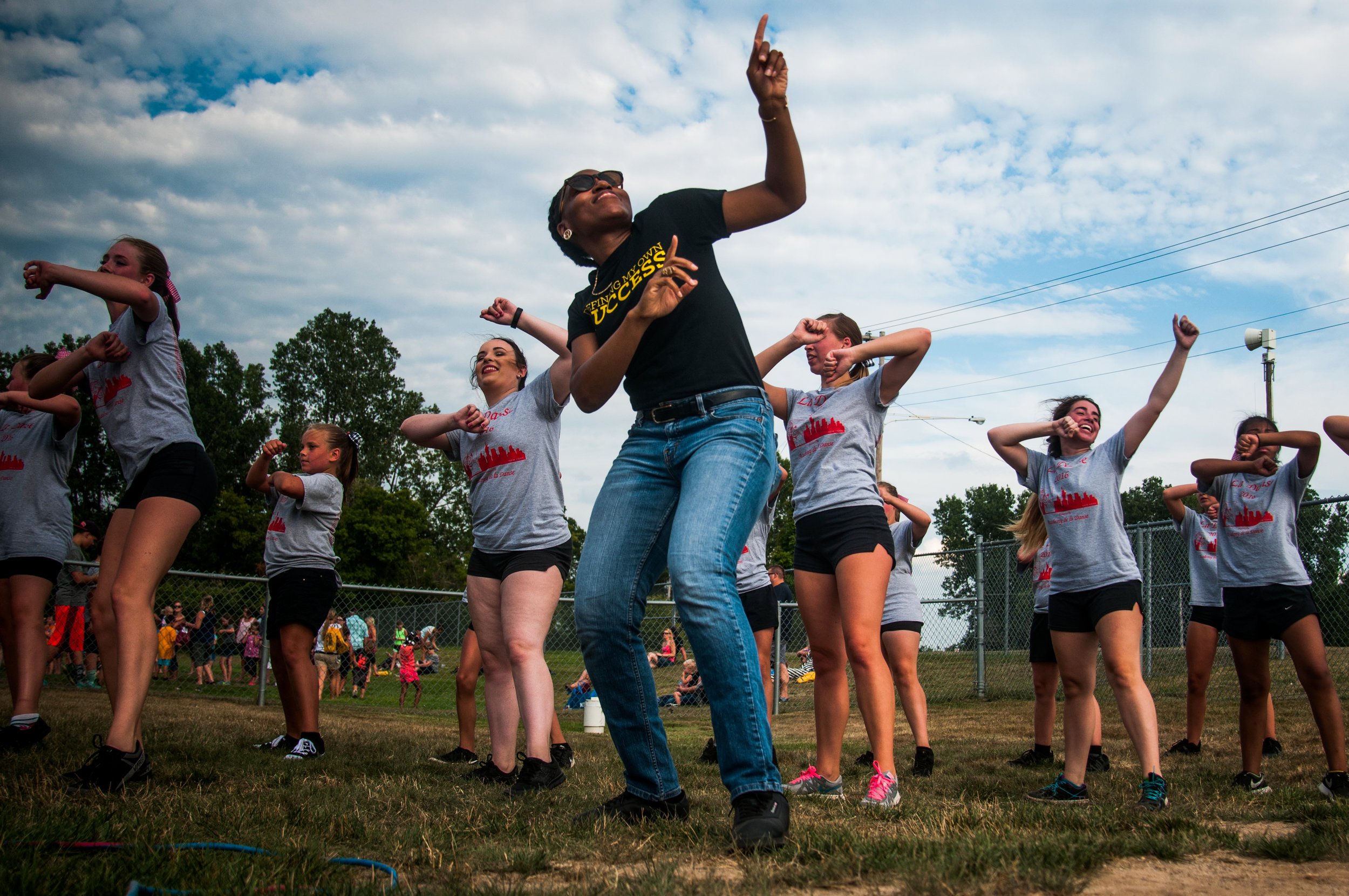 Nana Dompreh, of Flint, dances with the girls of De La Danse during the Davison Community Schools Back to School Blast on Tuesday, August 9, 2016 at Cardinal Stadium in Davison.