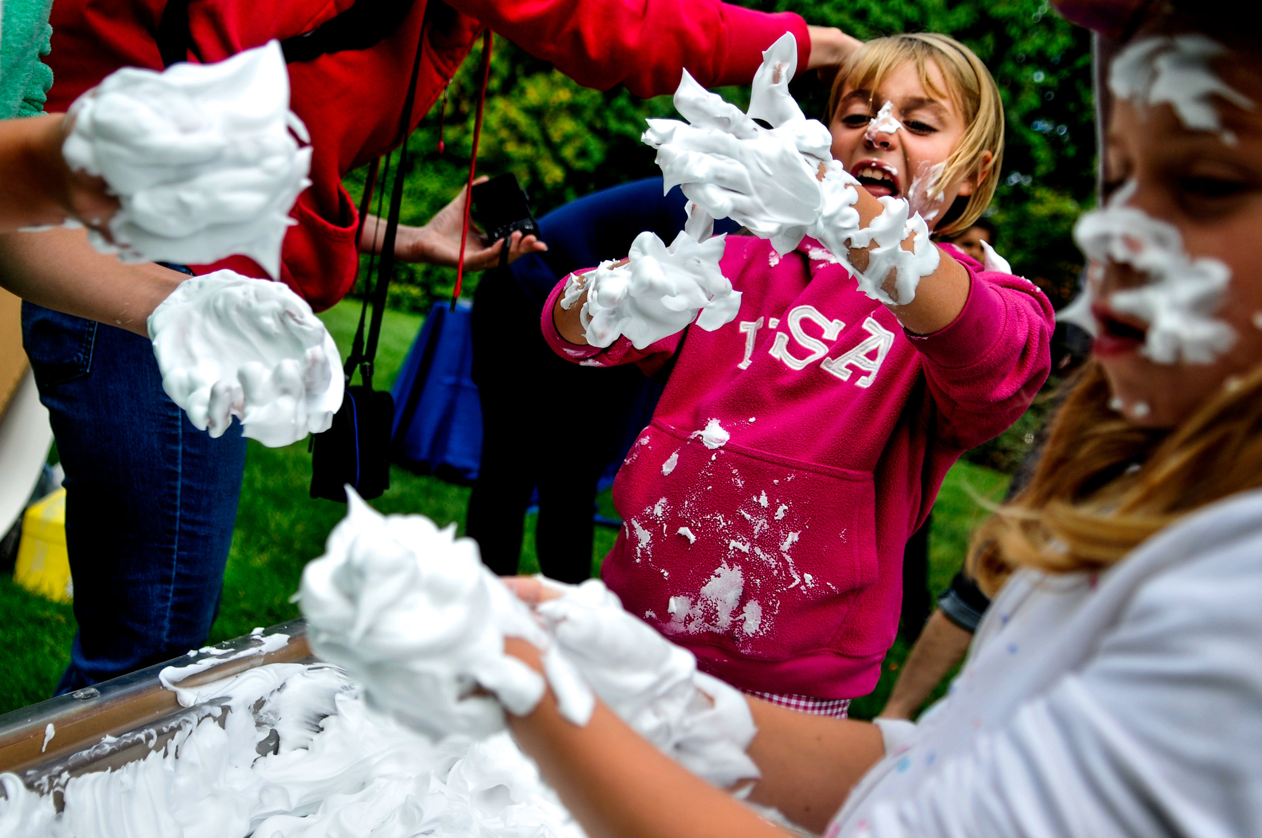 Anna Masen, 9, of Troy, plays in a box of shaving cream with her sisters during the 15th annual Fall Harvest Festival on Saturday, Sept. 24, 2016 at Applewood Estate in Flint.