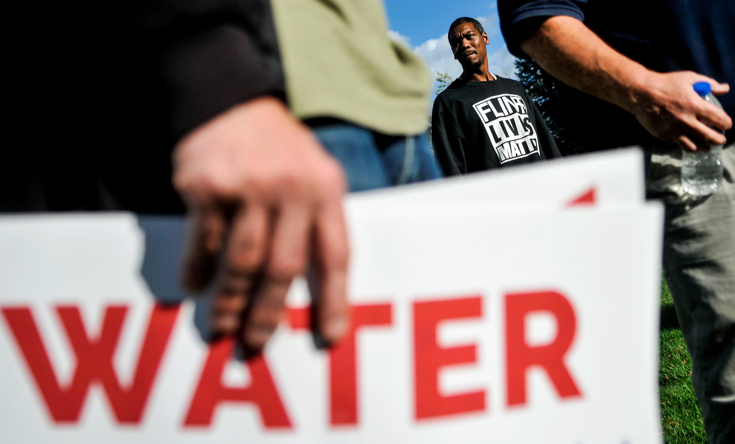 Flint resident Aaron Stinson, who had one of the highest lead levels recorded in Genesee County, center, stands with about a dozen people protesting the lack of action by the U.S. Senate and House regarding the Flint Water Crisis outside City Hall before the town council meeting Monday, Sept. 26, 2016 in downtown Flint.