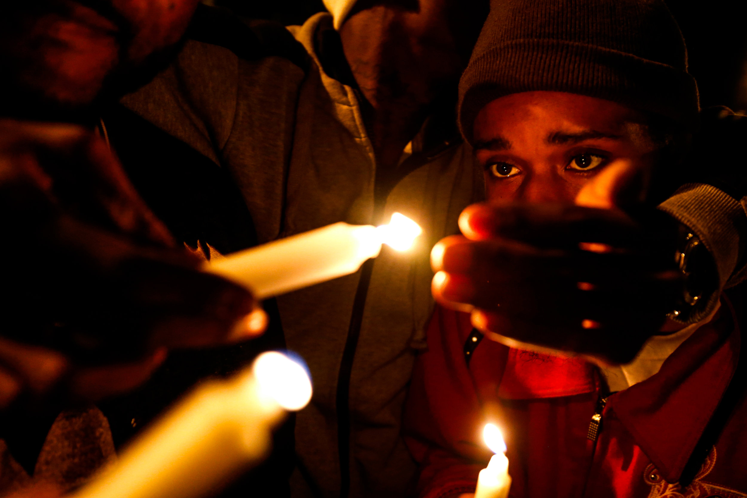 "James Mason Jr., a Flint native and long-time friend of Donte Williams, lights candles with other friends and family of Williams to remember and to celebrate his life during a vigil service on Sunday, Oct. 23, 2016 at the Flat Lot in downtown Flint, Mich. Earlier that day, Williams was shot multiple times and killed at the lot. ""We ain't have to be blood to be brothers,"" Mason said of his friend of almost 15 years. ""Sometime water is thicker than blood when you've been through the mud. That's how we was."""