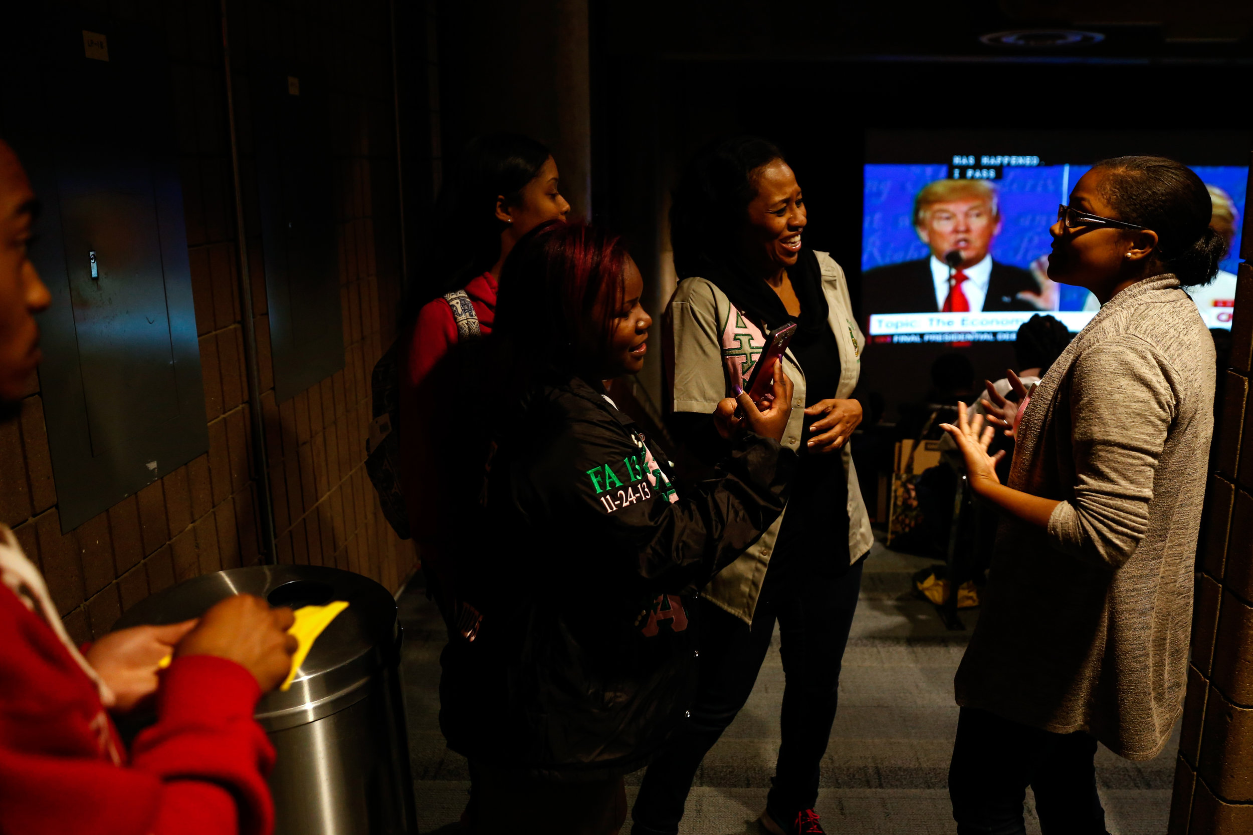 "Corey Taylor, a graduate advisor for Alpha Kappa Alpha Sorority, Inc., laughs while talking to Diamond Wilder, a senior at UM-Flint, right, while gathering with over 30 students, faculty, staff and community members in the Kiva to watch the Presidential debate on Wednesday, Oct. 19, 2016 at UM-Flint in downtown Flint. ""You need to be aware...and able to advocate for what you think is right for our country...and on a local level within your community,"" said Phaejare Thomas, president of Alpha Kappa Alpha Sorority, Incorperated Xi Chi chapter and a senior nursing student at UM-Flint."